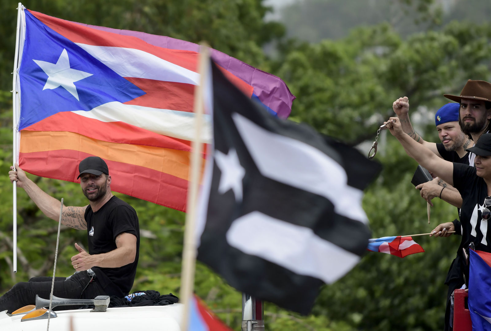 Puerto Rican singer Ricky Martin holds a Puerto Rico flag as he participates in a protest demanding the resignation of governor Ricardo Rossello, in San Juan, Puerto Rico, Friday, July 19, 2019.{ } (AP Photo/Carlos Giusti)