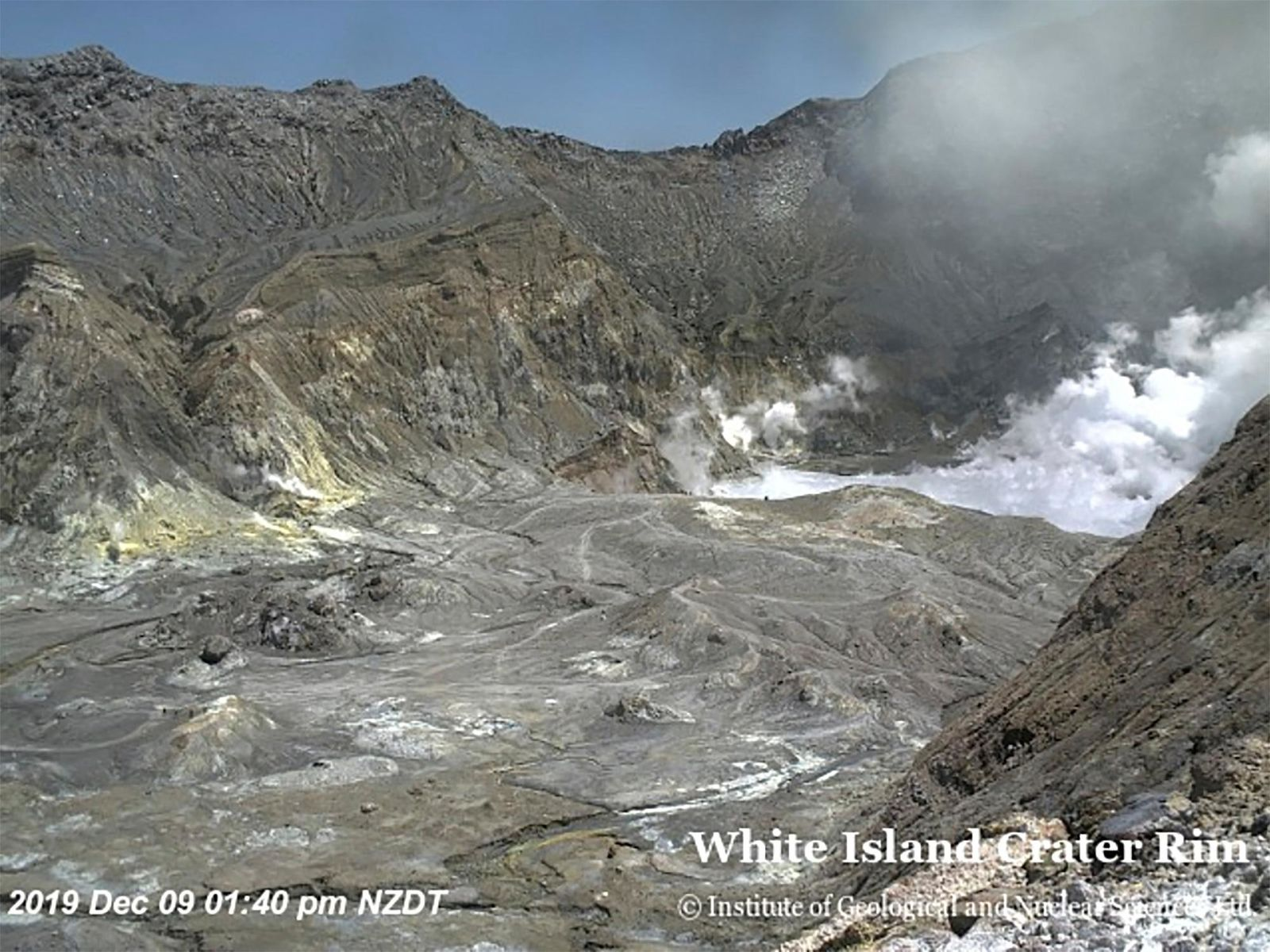 In this image released by GeoNet, tourists can be seen near the volcano's crater Monday, Dec. 9, 2019, on White Island, New Zealand.{ } (GNS Science via AP)