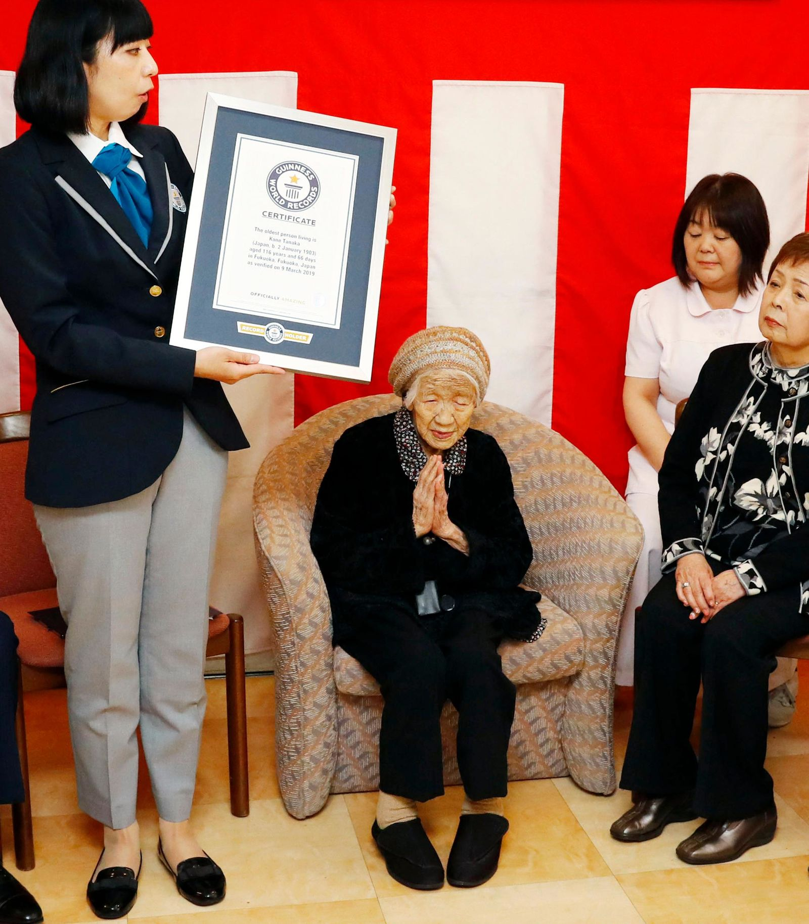 Kane Tanaka, a 116-year-old Japanese woman, puts her hands together as she receives a Guinness World Records certificate at a nursing home where she lives during a ceremony in Fukuoka, southwestern Japan, Saturday, March 9, 2019. Tanaka who loves playing the board game Othello was honored Saturday as the world's oldest living person by Guinness World Records. (Takuto Kaneko/Kyodo News via AP)