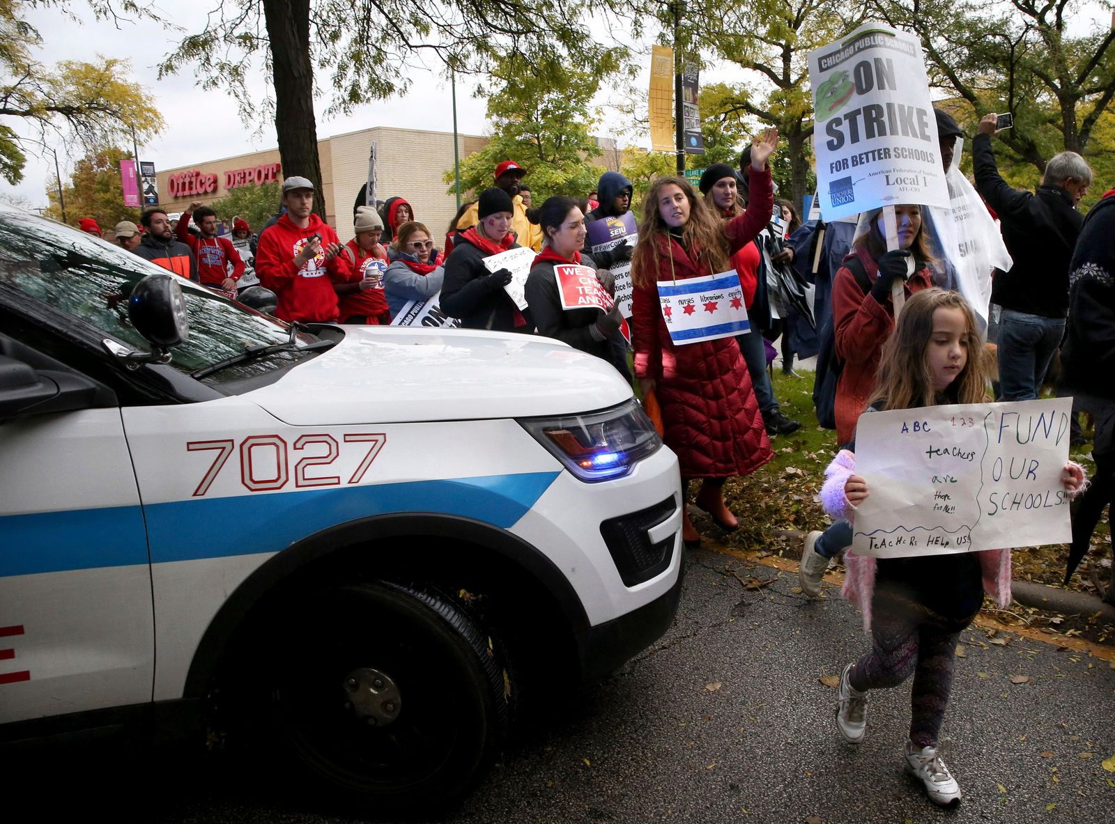 "Dozens of Chicago Teachers Union members, CPS students and supporters march around a police car blocking the street and continue to march through the streets of Chicago's Hyde Park neighborhood during the ""Nurse in Every School"" Solidarity March for Justice on Monday, Oct. 21, 2019. (Antonio Perez/Chicago Tribune via AP)"