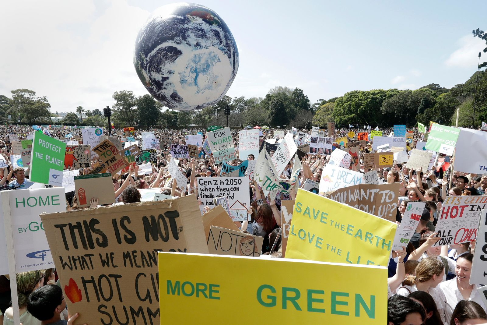 A large inflatable globe is bounced through the crowd as thousands of protestors, many of them school students, gather in Sydney, Friday, Sept. 20, 2019, calling for action to guard against climate change. s. (AP Photo/Rick Rycroft)