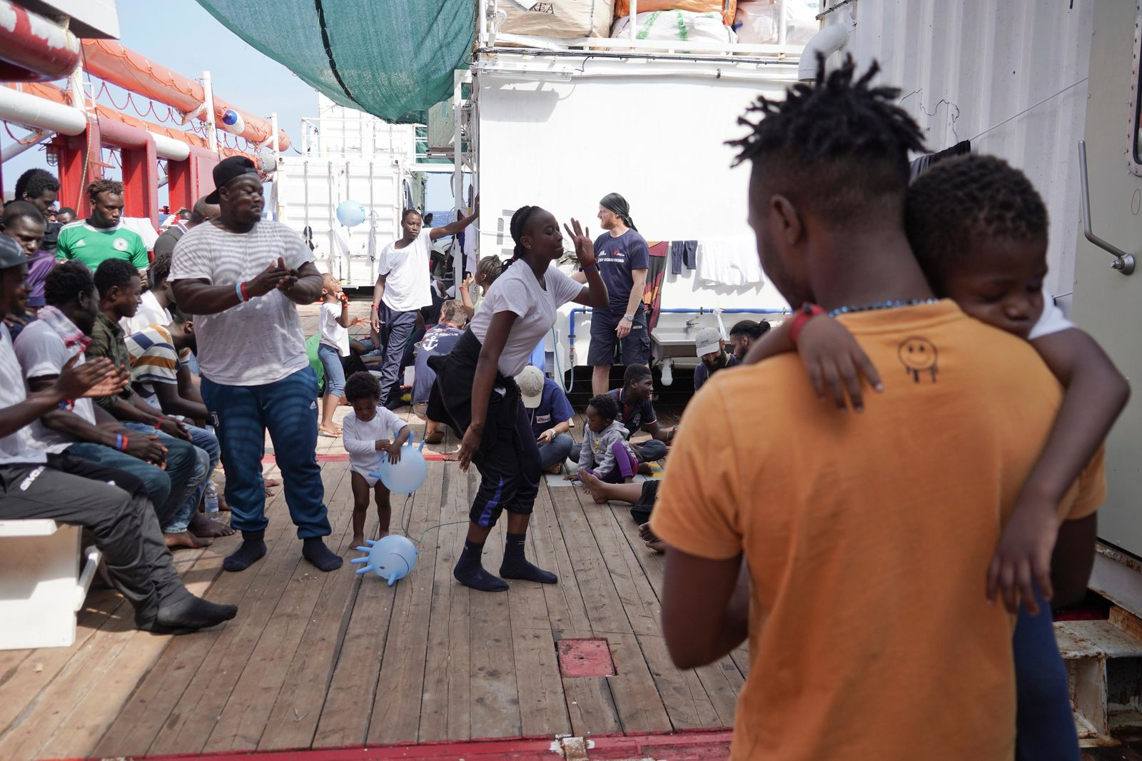 Rescued migrants dance and sing on the deck of the Ocean Viking as it sails in the Mediterranean Sea, Saturday, Sept. 21, 2019. The humanitarian ship operated by SOS Mediterranee and Doctors Without Borders is still waiting to be assigned a place of safety to disembark 182 people rescued after fleeing Libya. (AP Photo/Renata Brito)