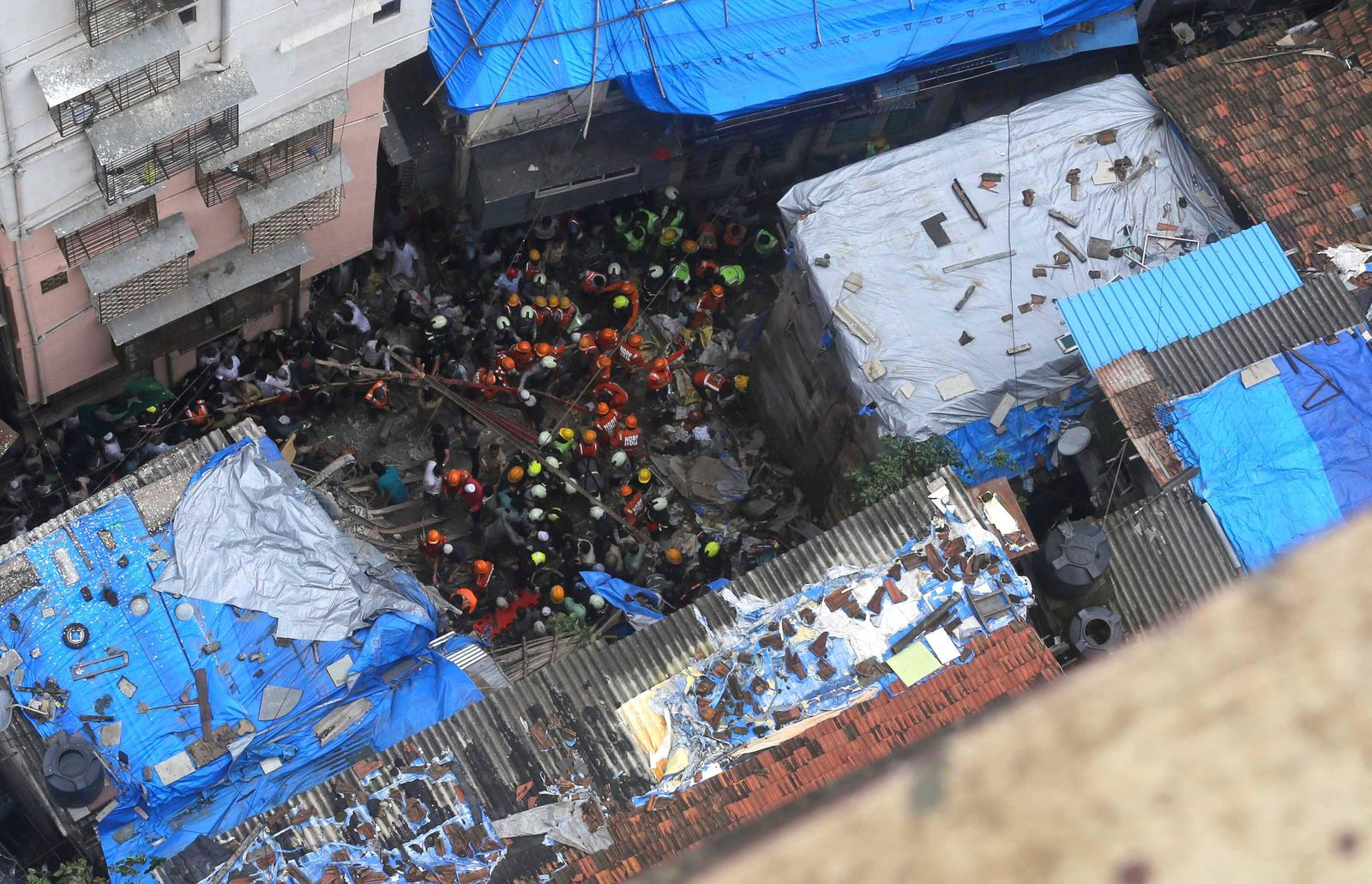 Rescuers work at the site of a building that collapsed in Mumbai, India, Tuesday, July 16, 2019. (AP Photo/Rajanish Kakade)