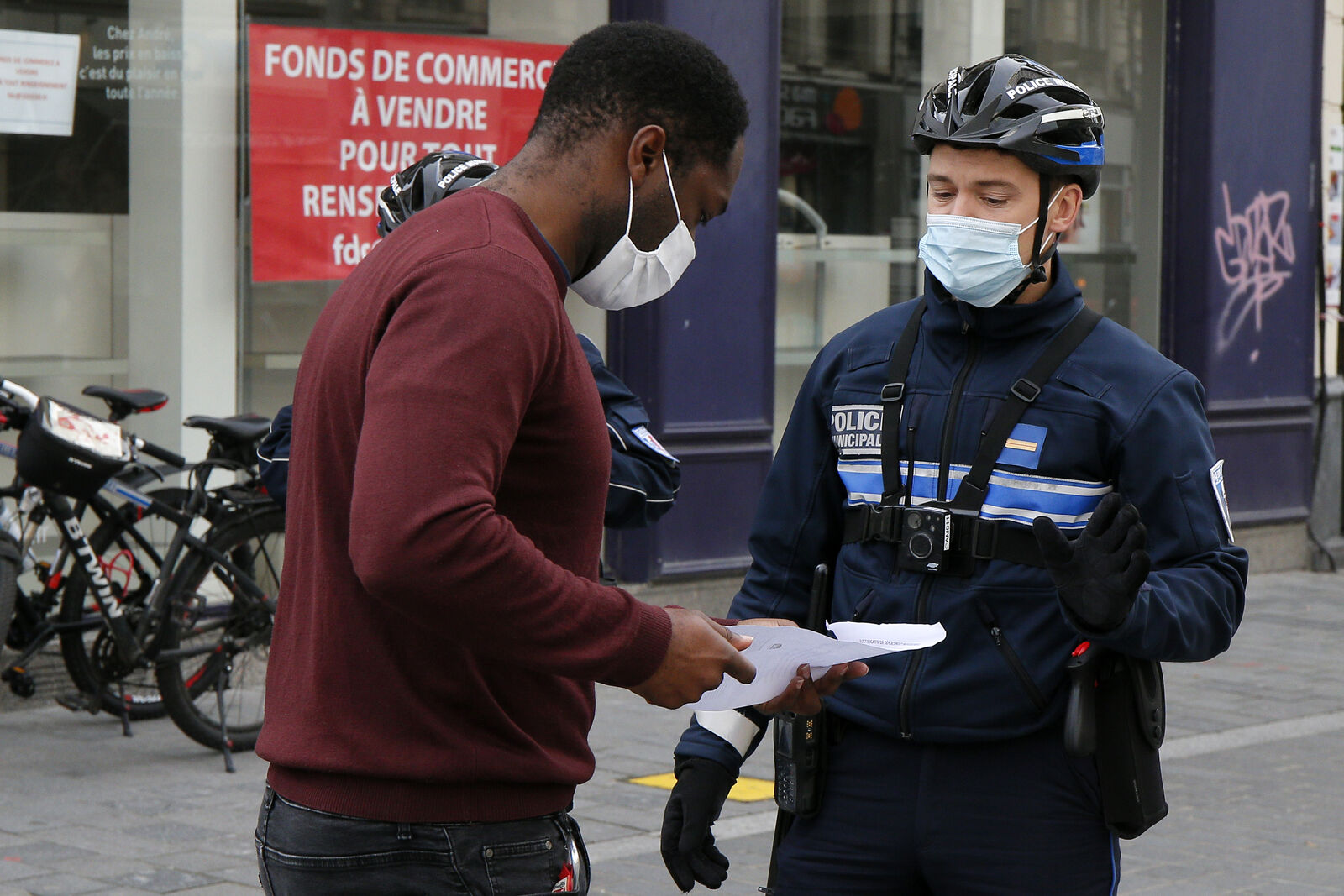 Policemen controls a resident in Lille northern France, Friday, Oct. 30, 2020. (AP Photo/Michel Spingler)