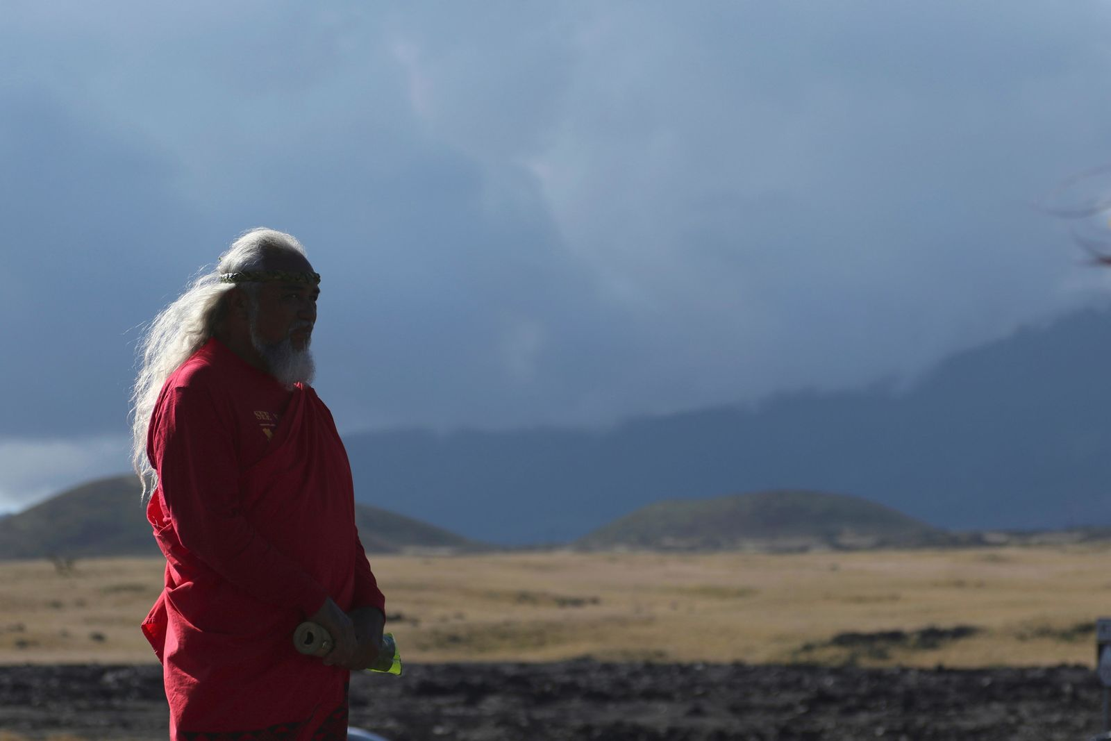 A native Hawaiian activist prays at the base of Hawaii's Mauna Kea on Sunday, July 14, 2019. Hundreds of demonstrators gathered at the base of Hawaii's tallest mountain to protest the construction of a giant telescope on land that some Native Hawaiians consider sacred. State and local officials will try to close the road to the summit of Mauna Kea Monday morning to allow trucks carrying construction equipment to make their way to the top. Officials say anyone breaking the law will be prosecuted. Protestors have blocked the roadway during previous attempts to begin construction and have been arrested. (AP Photo/Caleb Jones)