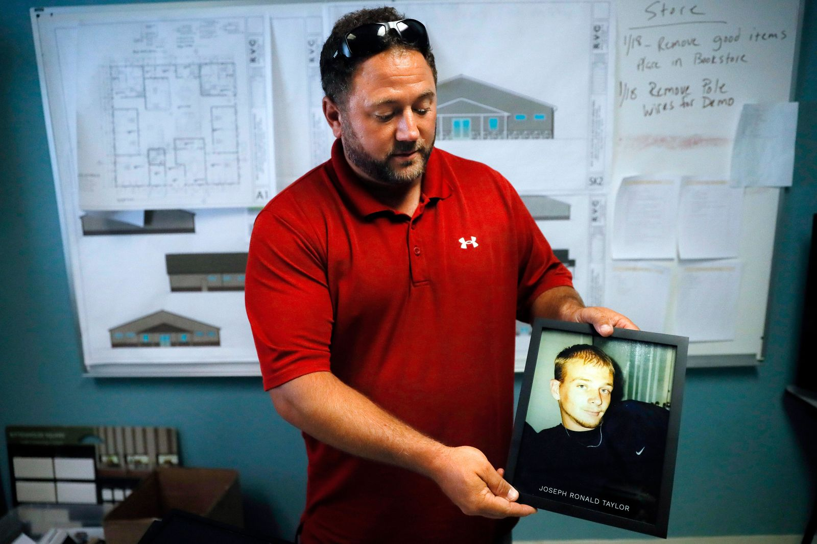 FILE - In this July 17, 2019, file photo Justin Oyer, executive director at Warriors 4 Christ, an addiction recovery center and program, holds an image of his cousin Joseph Ronald Taylor, who died from opioid addiction in Jackson, Ohio. (AP Photo/John Minchillo, File)