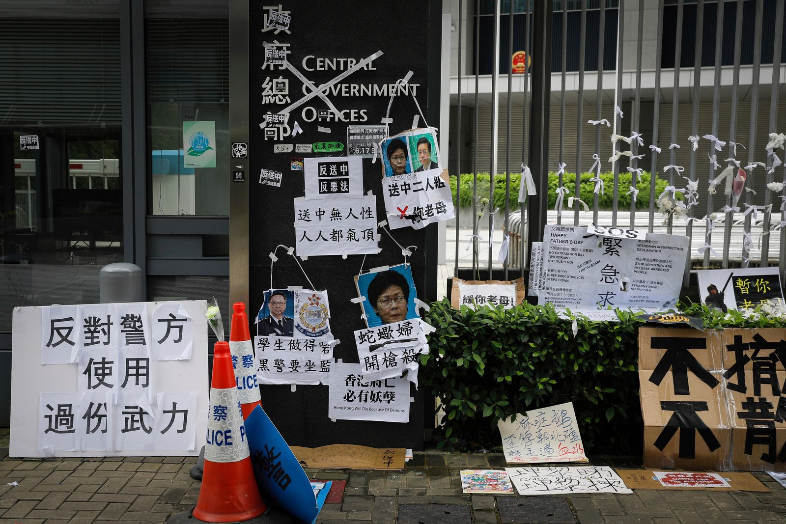 Posters and placards bearing photos of Hong Kong Chief Executive Carrie Lam and police commissioner Stephen Lo Wai-chung which left by protesters are placed outside the Legislative Council in Hong Kong, Tuesday, June 18, 2019. Hong Kong's government headquarters reopened Tuesday as the number of protesters outside dwindled to a few dozen and life returned to normal in the former British colony. (AP Photo/Vincent Yu)