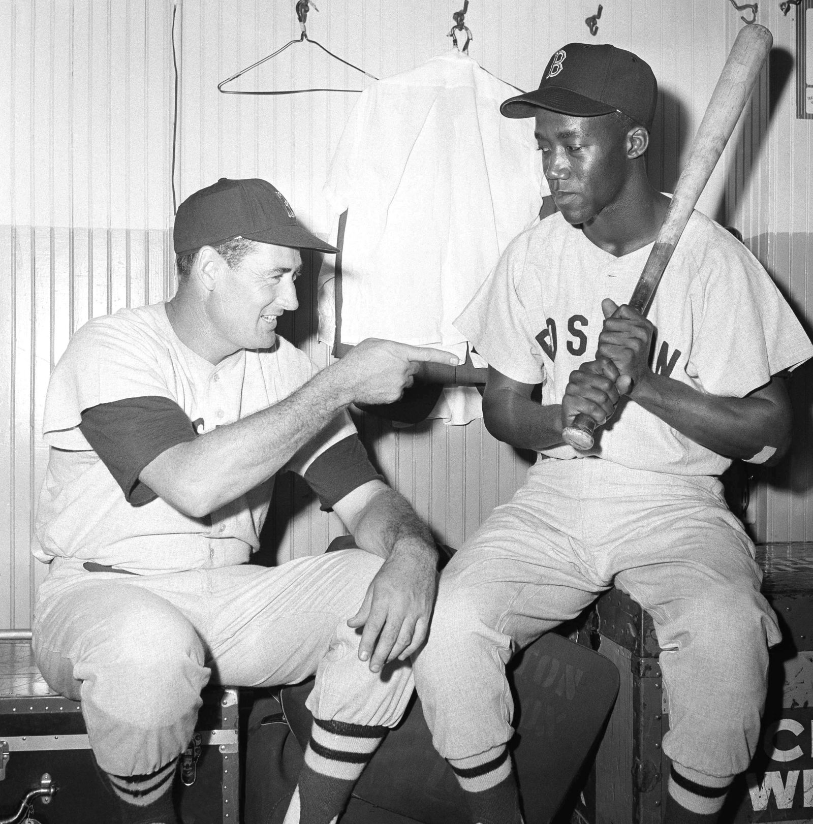 "FILE - In this July 1959 file photo, Elijah ""Pumpsie Green, right, an infielder who was recalled from the Minneapolis Farm club to join the Boston Red Sox, is given some friendly tips by Ted Williams in Chicago.  Green, the first black player on the Red Sox, has died. He was 85. A Red Sox spokesman confirmed his death Wednesday night, July 17, 2019. (AP Photo/Ed Maloney)"