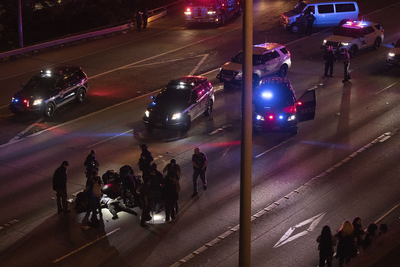 Emergency workers tend to an injured person on the ground after a driver sped through a protest-related closure on the Interstate 5 freeway in Seattle, authorities said early Saturday, July 4, 2020. (James Anderson via AP)