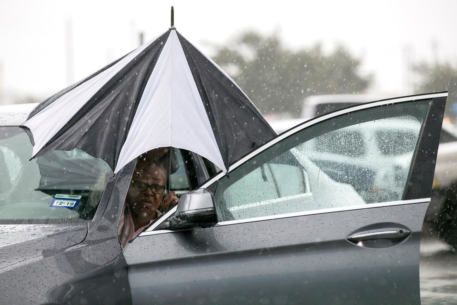 A woman closes her umbrella after getting into her car during a rain storm stemming from rain bands spawned by Tropical Storm Imelda near I-45 and Almeda-Genoa on Tuesday, Sept. 17, 2019, in Houston. (Brett Coomer/Houston Chronicle via AP)/Houston Chronicle via AP