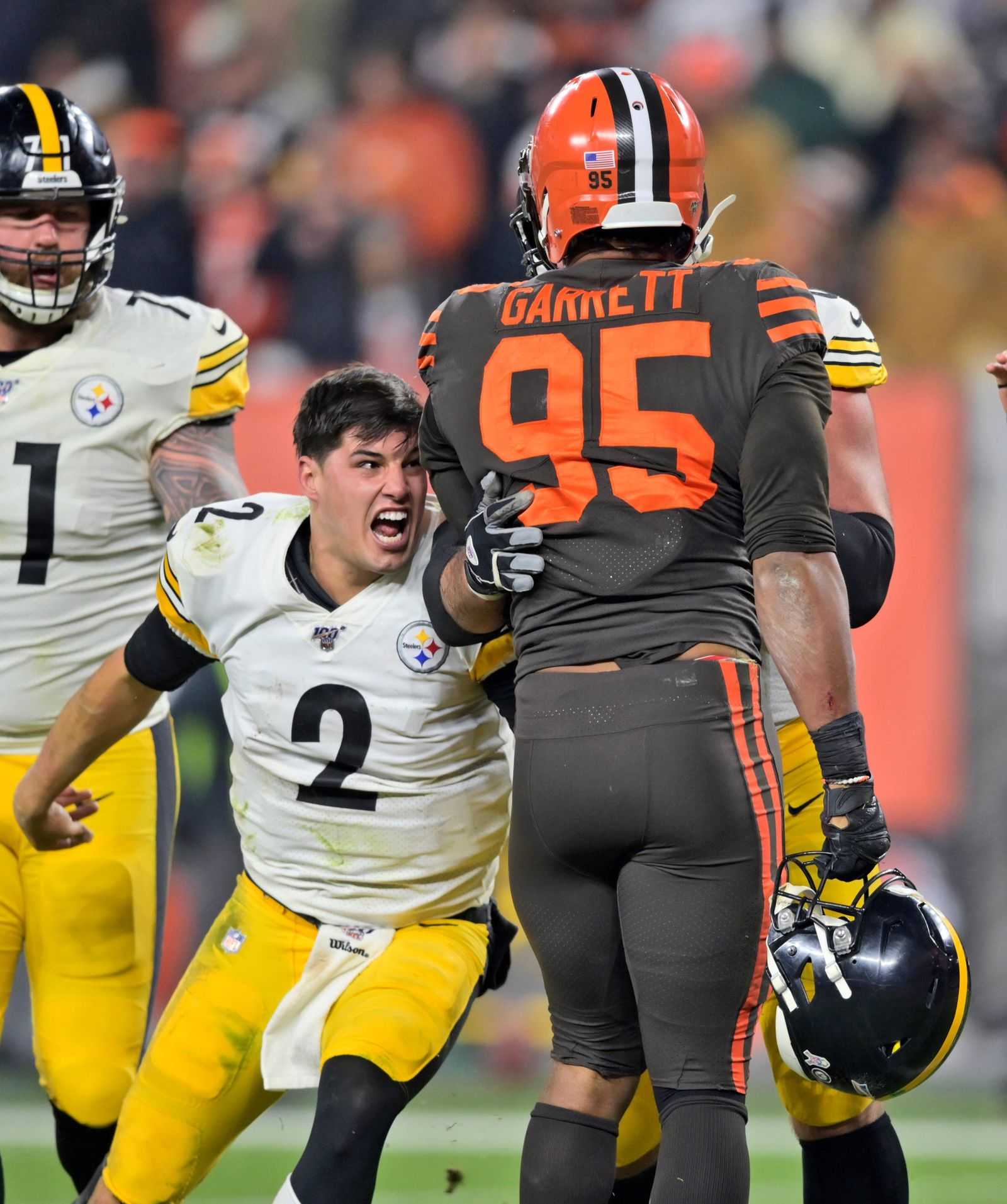 Pittsburgh Steelers quarterback Mason Rudolph (2) goes after Cleveland Browns defensive end Myles Garrett (95) during the second half of an NFL football game Thursday, Nov. 14, 2019, in Cleveland. The Browns won 21-7. (AP Photo/David Richard)