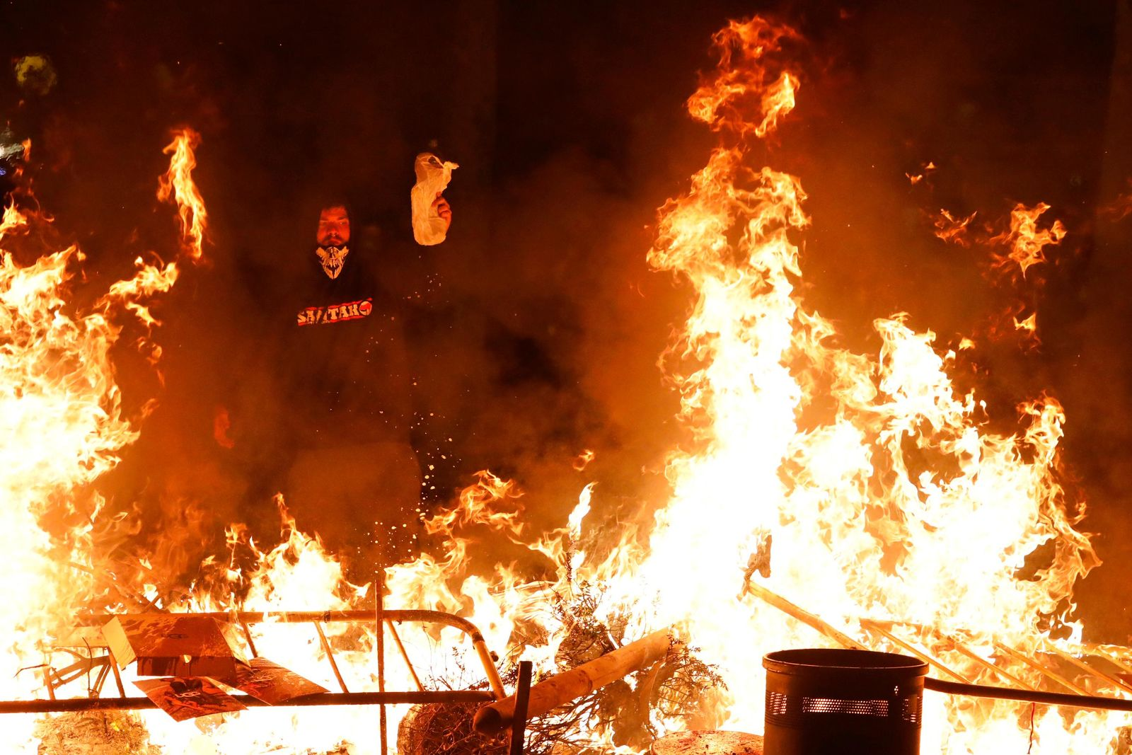 A protestors pours gasoline on a burning barricade during clashes with police in Barcelona, Spain, Thursday, Oct. 17, 2019.{ } (AP Photo/Emilio Morenatti)