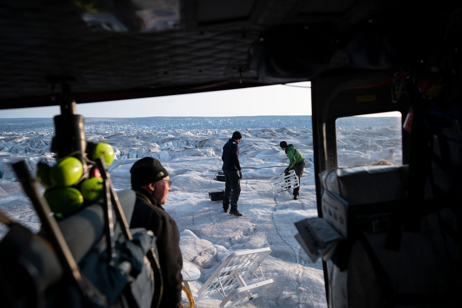 In this Aug. 16, 2019, photo, New York University air and ocean scientist David Holland, left, and field safety officer Brian Rougeux, right, are helped by pilot Martin Norregaard as they carry antennas out of a helicopter to be installed at the Helheim glacier, in Greenland.{ } (AP Photo/Felipe Dana)