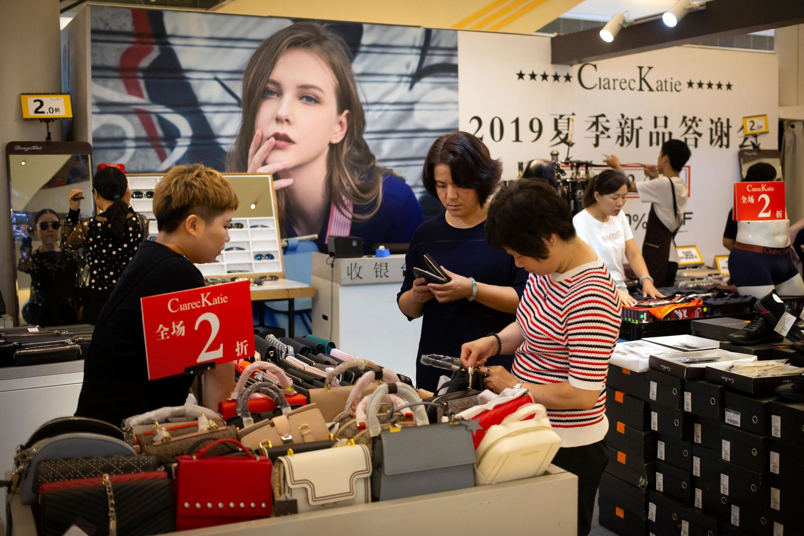 Shoppers browse goods for sale at a discount retailer in a shopping mall in Beijing, Friday, Aug. 2, 2019. (AP Photo/Mark Schiefelbein)
