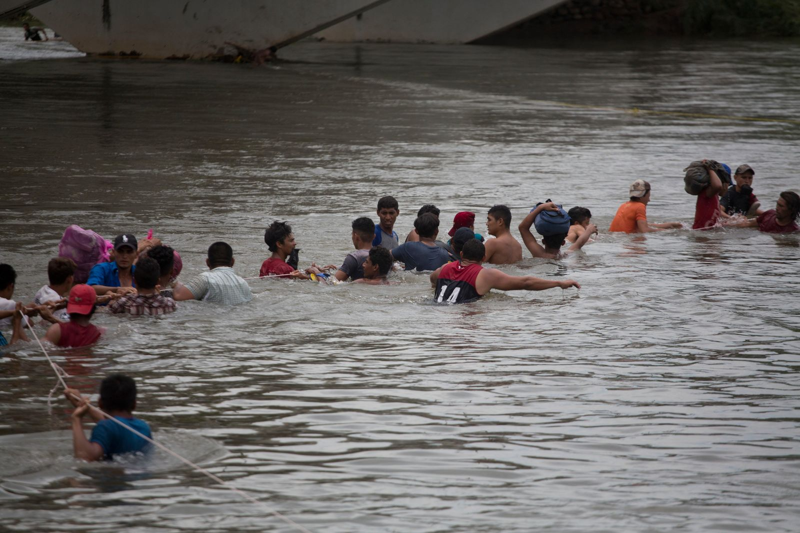 A group of Central American migrants wade across the Suchiate River, on the the border between Guatemala and Mexico, in Ciudad Hidalgo, Mexico, Saturday, Oct. 20, 2018.{ } (AP Photo/Moises Castillo)