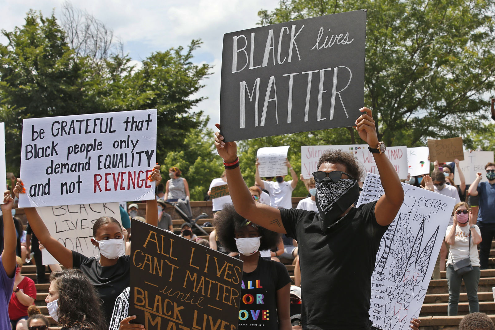 "Atlanta Hawks guard Trae Young, right, holds a ""Black Lives Matter"" sign at a peaceful rally Monday, June 1, 2020, in his hometown of Norman, Okla., calling attention to the killing of George Floyd by Minneapolis police on May 25. (AP Photo/Sue Ogrocki)"