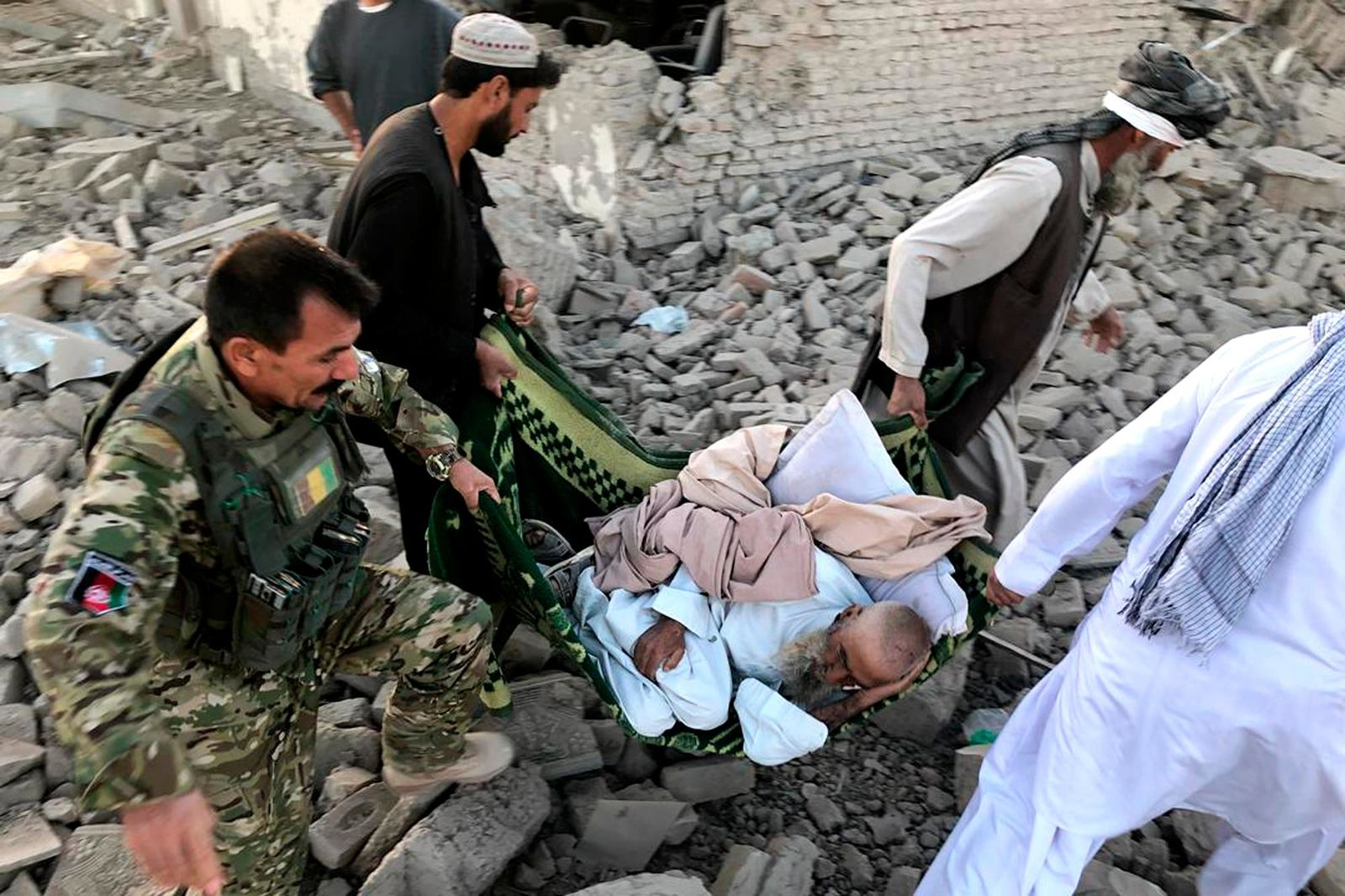 An Afghan security member and people carry an injured man after a suicide attack in Zabul, Afghanistan, Thursday, Sept. 19, 2019. A powerful early morning suicide truck bomb devastated a hospital in southern Afghanistan on Thursday. (AP Photo/Ahmad Wali Sarhadi)