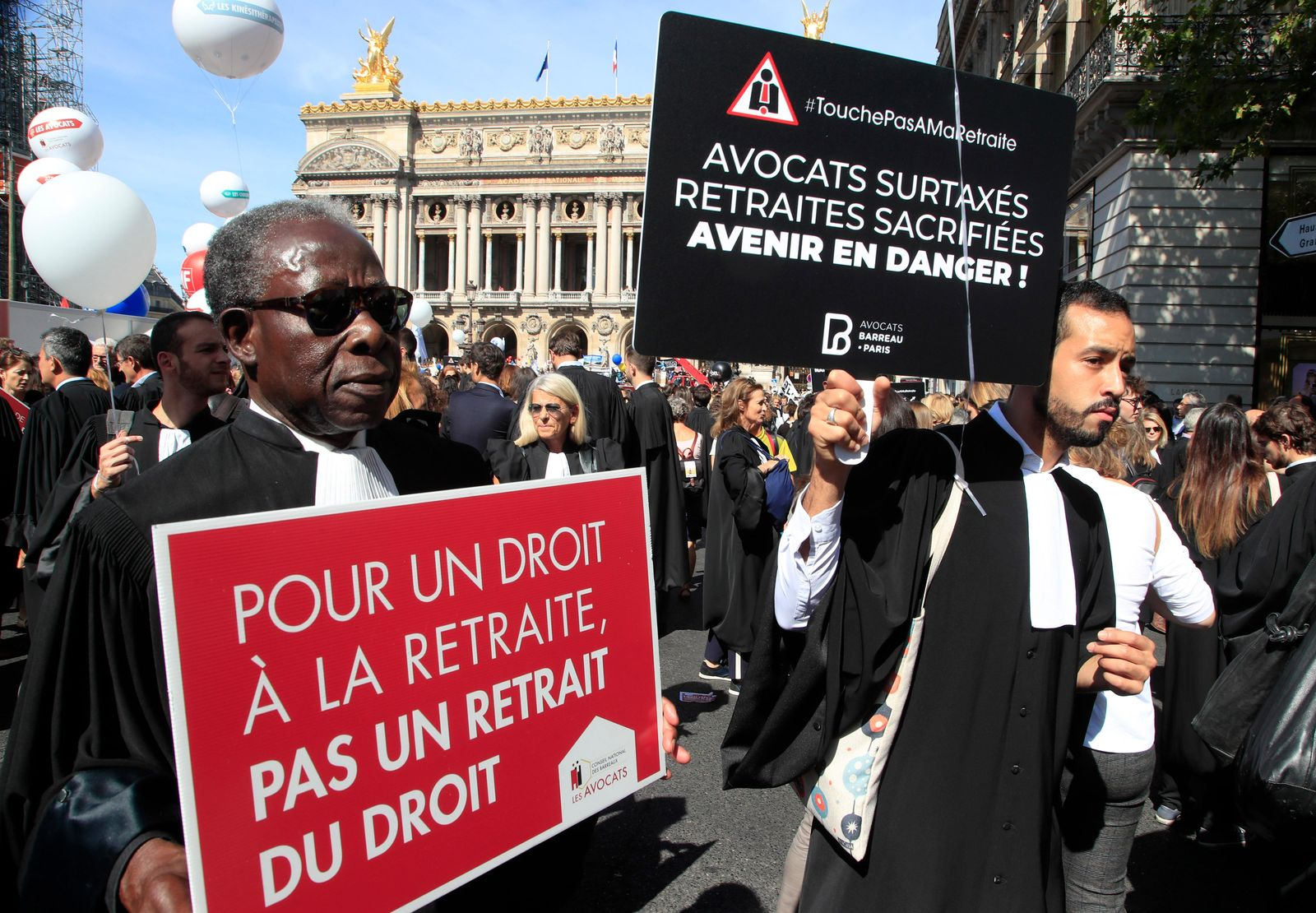"Lawyers march with placards during a protest against the planned pension change in Paris, Monday, Sept. 16, 2019. French lawyers, doctors, nurses, pilots and others are taking to the streets of Paris to protest planned pension changes by French President Emmanuel Macron's government. Placards read, ""to have the right on pension and not a pension of law"", left, ""lawyers over taxed, pension scarified, future in danger"". (AP Photo/Michel Euler)"