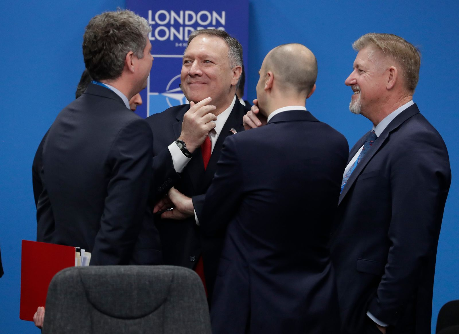 Secreatary of State Mike Pompeo, center, smiles as he arrives to participate in a round table meeting during a NATO leaders meeting at The Grove hotel and resort in Watford, Hertfordshire, England, Wednesday, Dec. 4, 2019. (AP Photo/Evan Vucci)