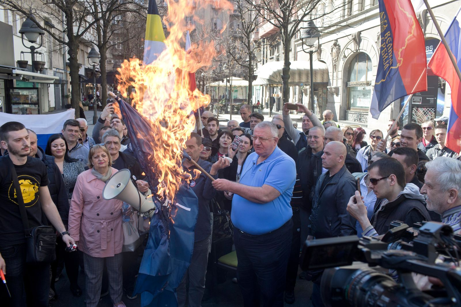 Vojislav Seselj, center, the leader of the ultranationalist Serbian Radical Party, holds a burning NATO flag as he and others gather for a protest in Belgrade, Serbia, Sunday, March 24, 2019.{ } (AP Photo/Marko Drobnjakovic)