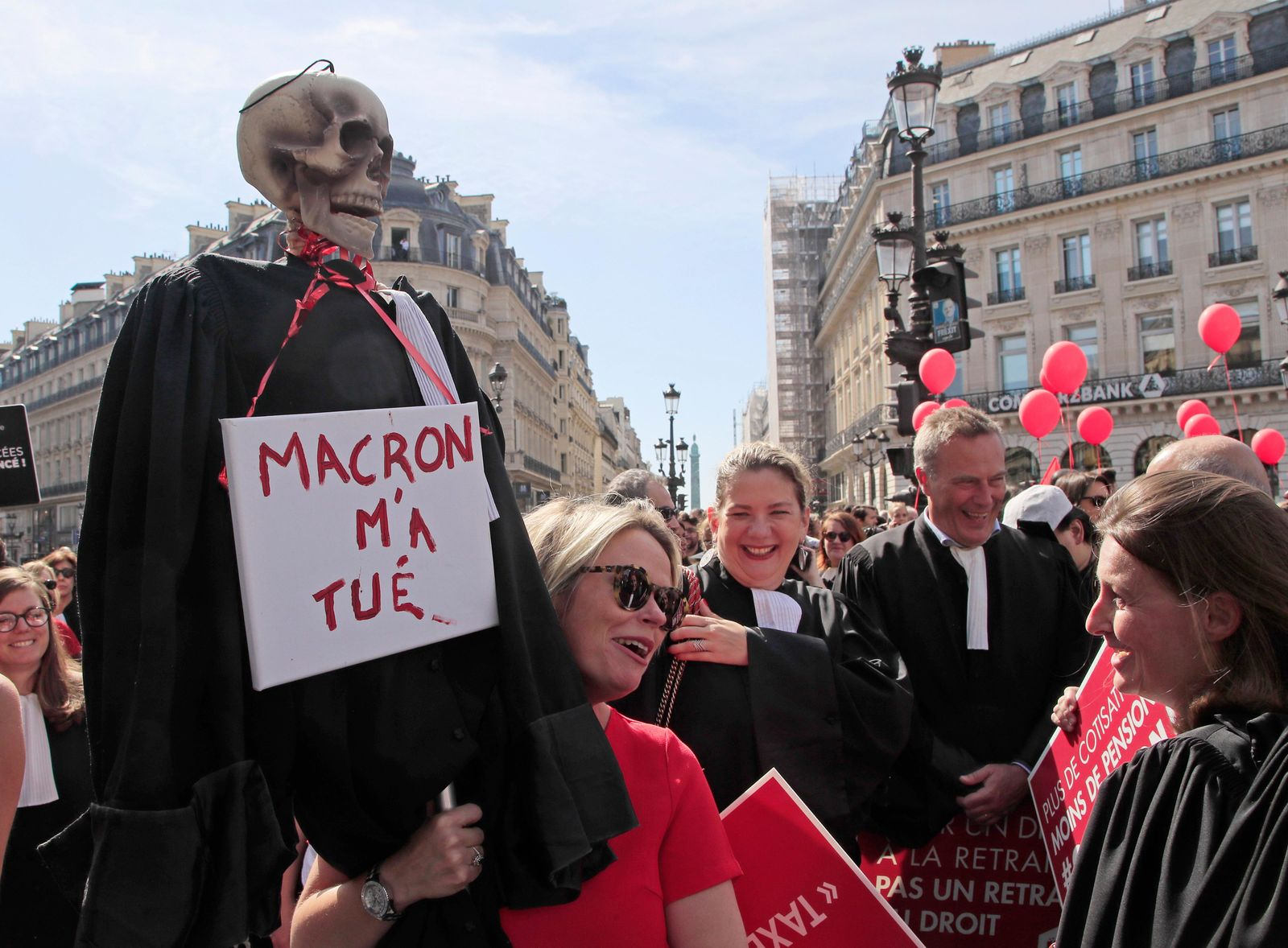 "A lawyer holds a effigy with a scull represending a dead lawyer march during a protest against the planned pension change in Paris, Monday, Sept. 16, 2019. French lawyers, doctors, nurses, pilots and others are taking to the streets of Paris to protest planned pension changes by French President Emmanuel Macron's government. Placard read, ""no to the pension tax"". Placard reads, ""Macron wants my dead"". (AP Photo/Michel Euler)"