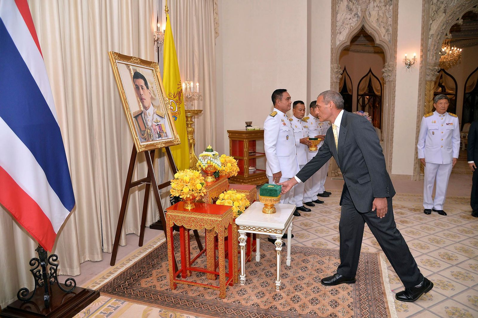In this photo released by Government Spokesman Office, Craig Challen, an Australian member of the Thai cave rescue team, receives the Member of the Most Admirable Order of the Direkgunabhorn in front of a portrait of Thailand's King Maha Vajiralongkorn Bodindradebayavarangkun during the royal decoration ceremony at the Royal Thai Government House in Bangkok, Thailand, Friday, April 19, 2019. (Government Spokesman Office via AP)