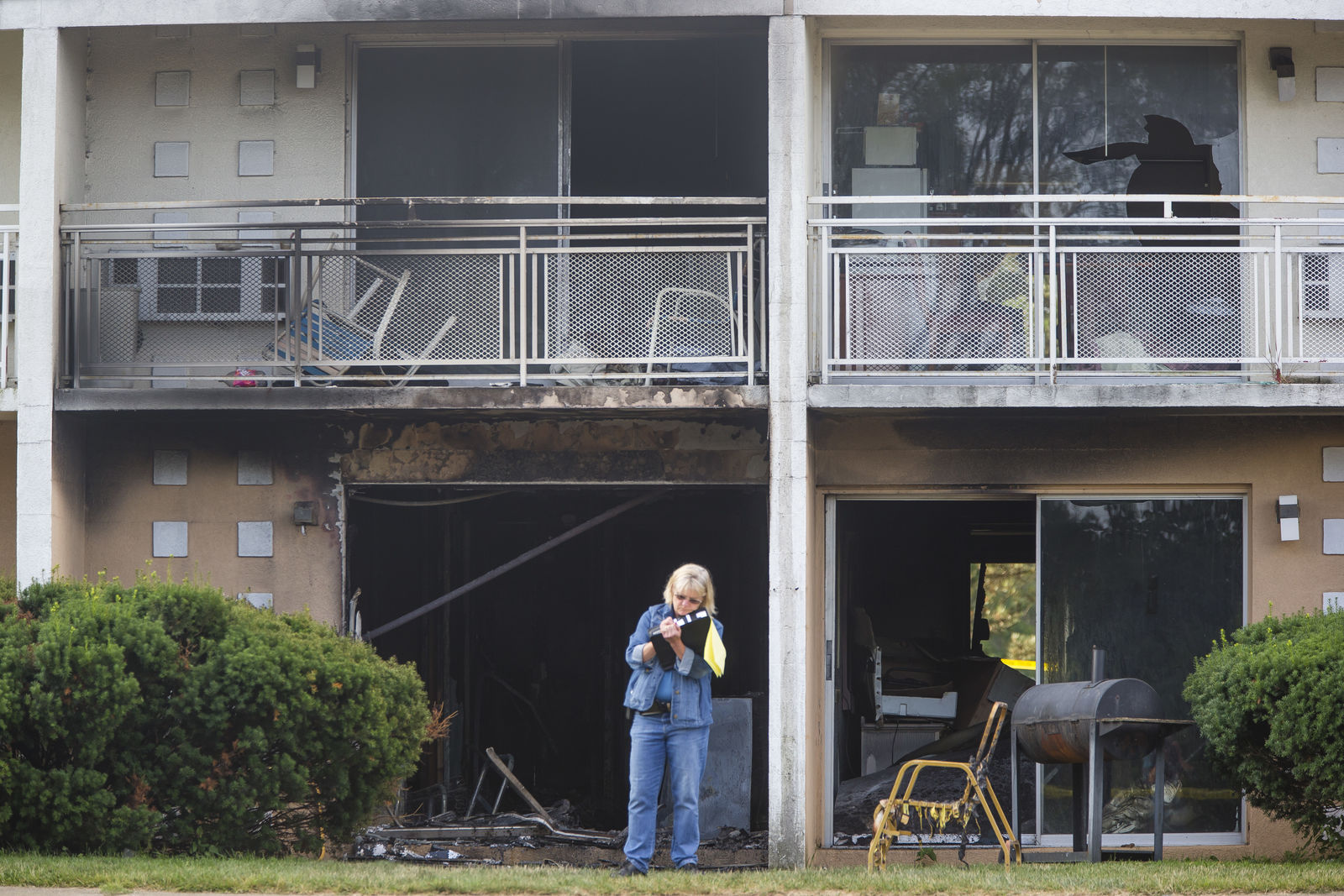 Berrien County Sheriff's Detective Cathy Easton takes notes at the scene of a fire at the Cosmo Extended Stay Motel in Sodus Township, Mich., on Saturday, July 28, 2018.  A fire swept through the southwestern Michigan motel early Saturday, killing several members of the same family, including a woman and her children, authorities said.   (Michael Caterina/South Bend Tribune via AP)
