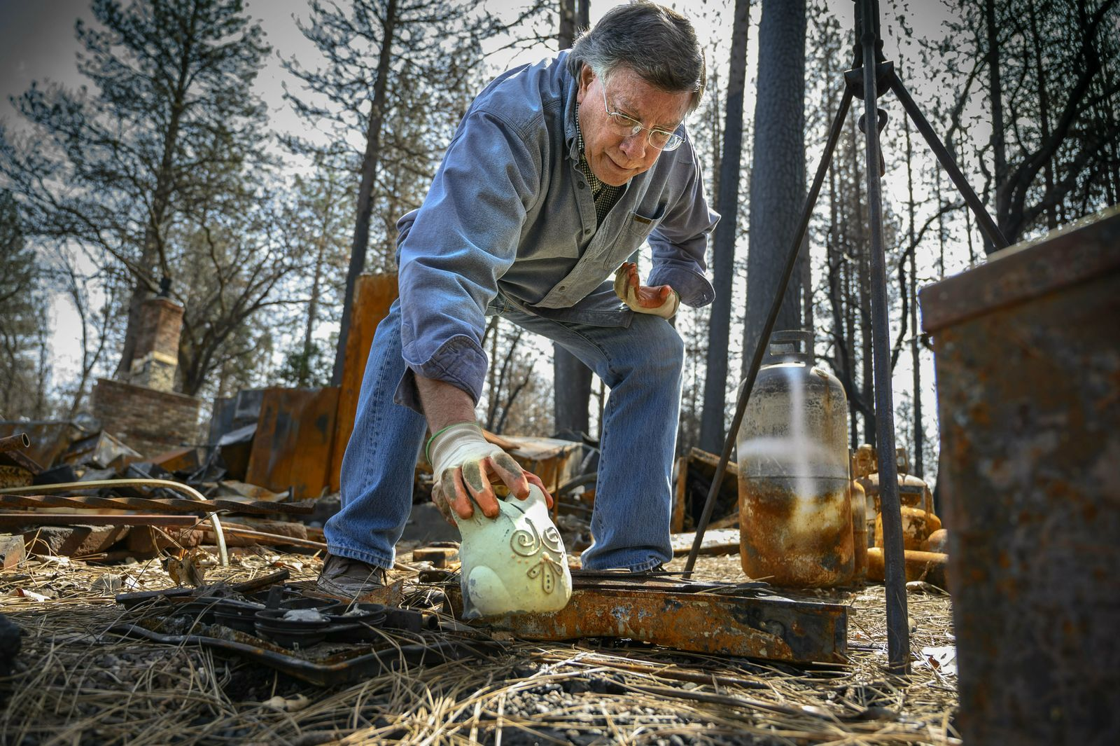 In this March 24, 2019, photo, Gene Mapa collects metal and ceramic objects that didn't burn in the Camp Fire at his house in Paradise, Calif. Mapa now lives in Colfax, which as a similar level of fire risk. (Hector Amezcua/The Sacramento Bee via AP)