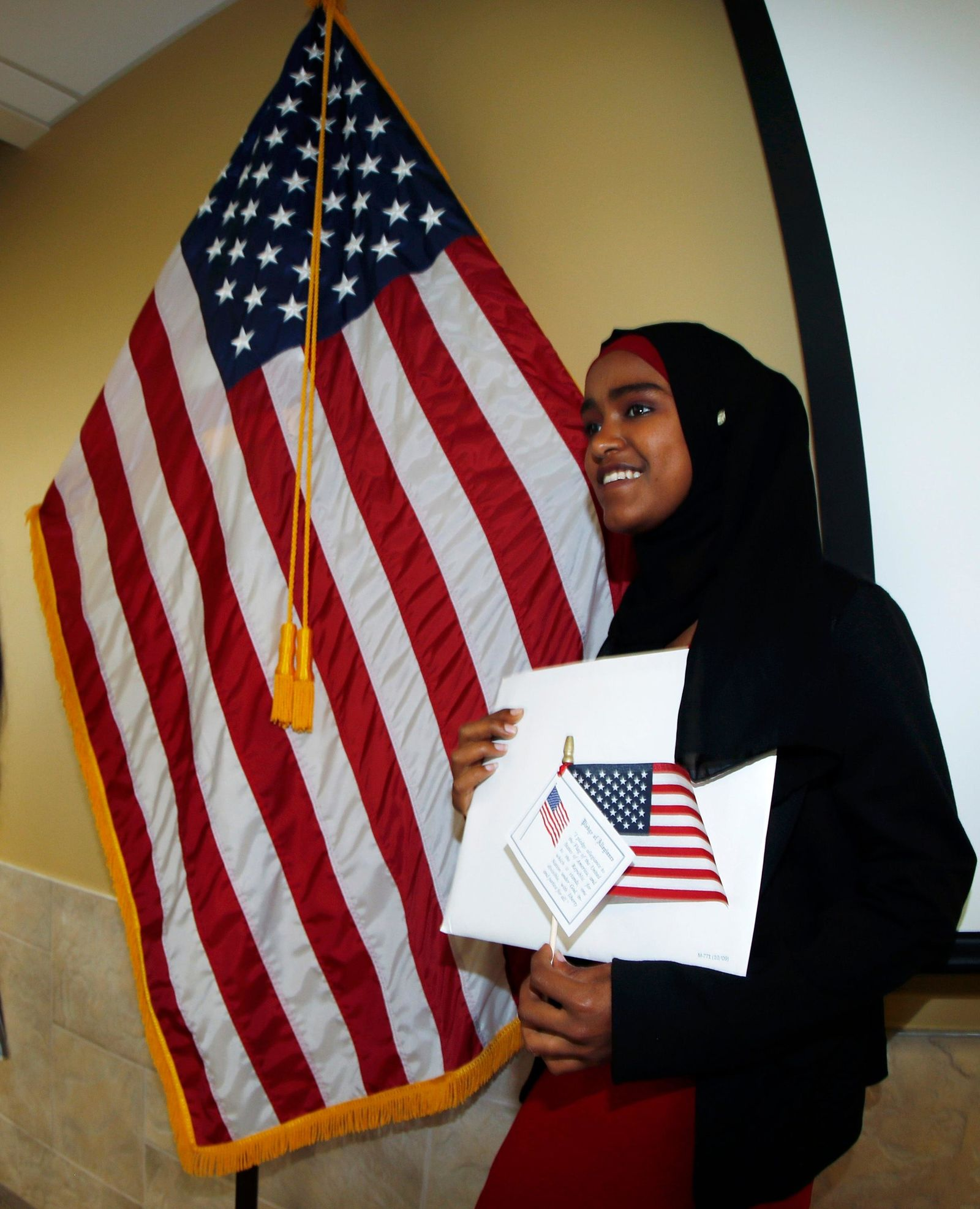 Safu Abdulhakim, who was born in Ethiopia, stands next to an American flag after she was granted her citizenship in the United States at a naturalization ceremony, Thursday, May 16, 2019, in Centennial, Colo. (AP Photo/David Zalubowski)
