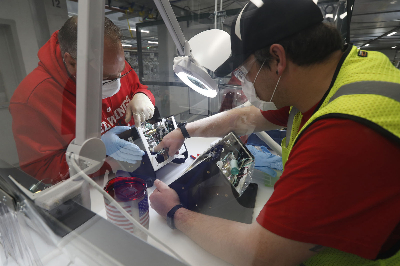 Ford Motor Co., team leader Kyle Lenart, right, inspects a ventilator that the automaker is assembling at the Ford Rawsonville plant, Wednesday, May 13, 2020 in Ypsilanti Township, Mich. (AP Photo/Carlos Osorio)