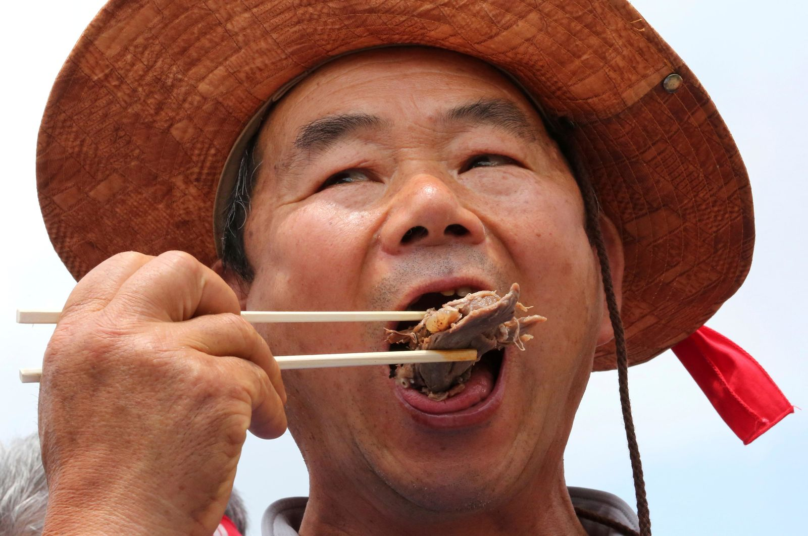 A member of the Korean Dog Meat Association eats dog meat during a rally to support eating the meat in front of the National Assembly in Seoul, South Korea, Friday, July 12, 2019. July 12 is the day South Koreans eat healthy foods such as dog meat in the belief it would help them survive heat during summer. (AP Photo/Ahn Young-joon)