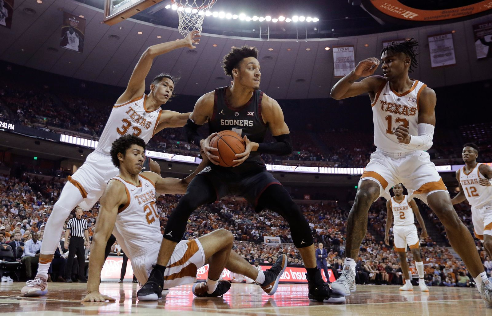 Oklahoma center Jamuni McNeace (4) grabs a rebound in front of Texas forward Kamaka Hepa (33), forward Jericho Sims (20) and guard Jase Febres (13) during the first half of an NCAA college basketball game, in Austin, Texas, Saturday, Jan. 19, 2019. (AP Photo/Eric Gay)