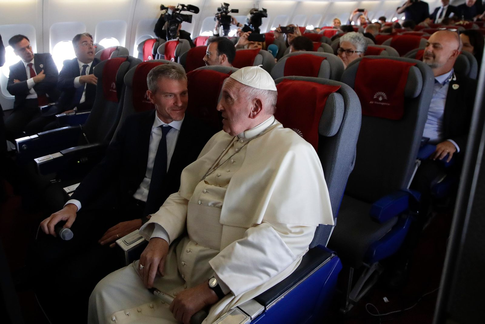 Pope Francis talks with his spokesperson Matteo Bruni, as they take a break during a moment of turbulence during a press conference on his way back from Antamanarivo to Rome, Tuesday, Sept. 10, 2019, after his seven-day pastoral trip to Mozambique, Madagascar, and Mauritius. (AP Photo/Alessandra Tarantino)
