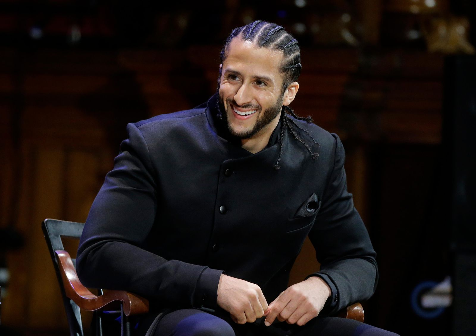 FILE - In this Oct. 11, 2018, file photo, former NFL football quarterback Colin Kaepernick smiles on stage during W.E.B. Du Bois Medal ceremonies at Harvard University, in Cambridge, Mass. Kaepernick plans to audition for NFL teams on Saturday, Nov. 16, 2019, in a private workout arranged by the league to be held in Atlanta. (AP Photo/Steven Senne, File)