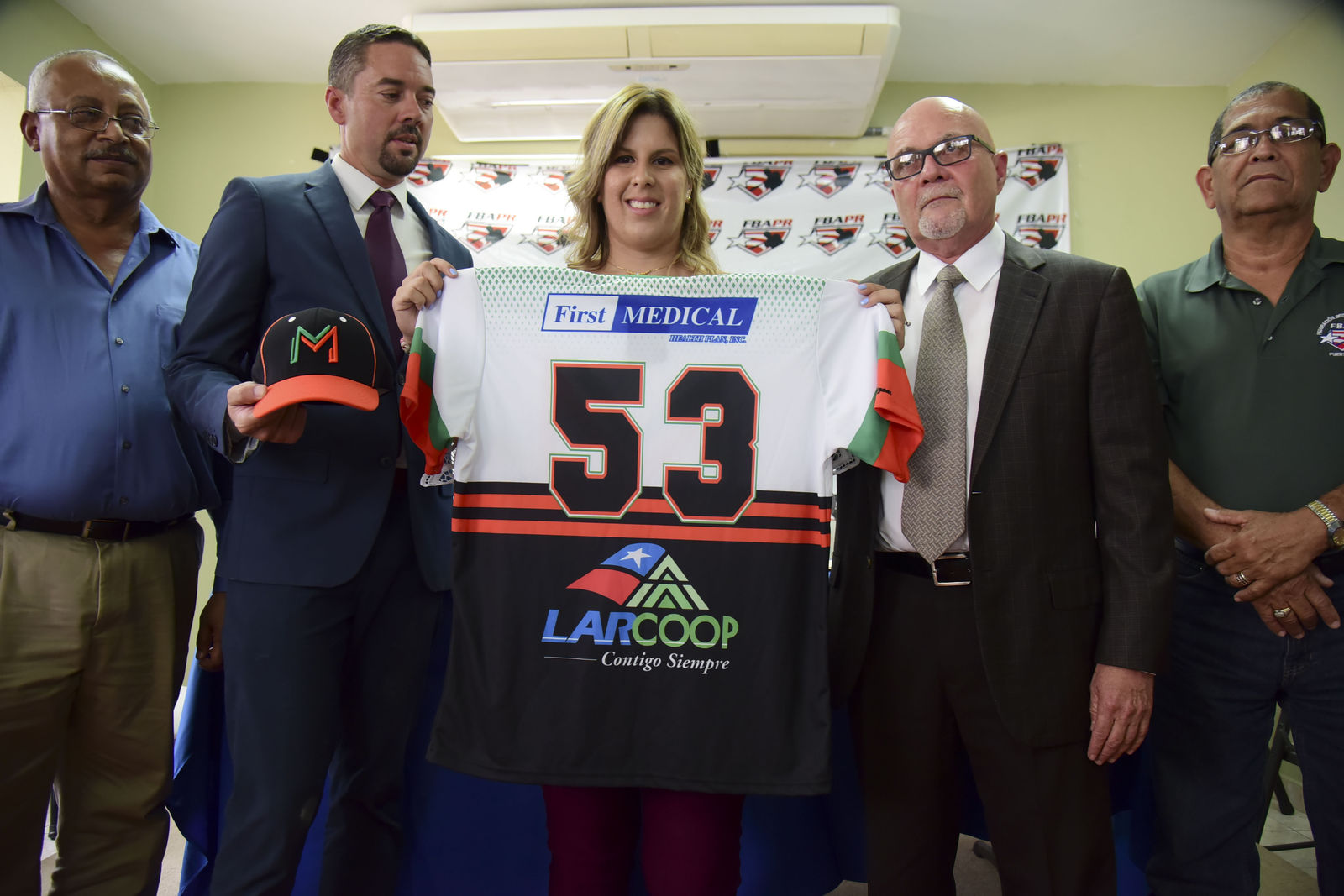 First baseman and member of the National Women's Baseball Team, Diamilette Quiles Alicea, center, is presented as the first female player to sign with The Utuado Highlanders, one of the teams that participate in the Superior Double A Baseball League, in San Juan, Puerto Rico, Thursday, May 16, 2019. Quiles Alicea shows the team's colors accompanied by the executive director of the League, Pedro Vargas, left, the representative of the Montaneses of Utuado Rafael Juarbe, second left, the president of the Federation, Dr. Jose Quiles Rosas, second right, and the executive director of the Women's Baseball League, José Rafael Torres. (AP Photo/Carlos Giusti)