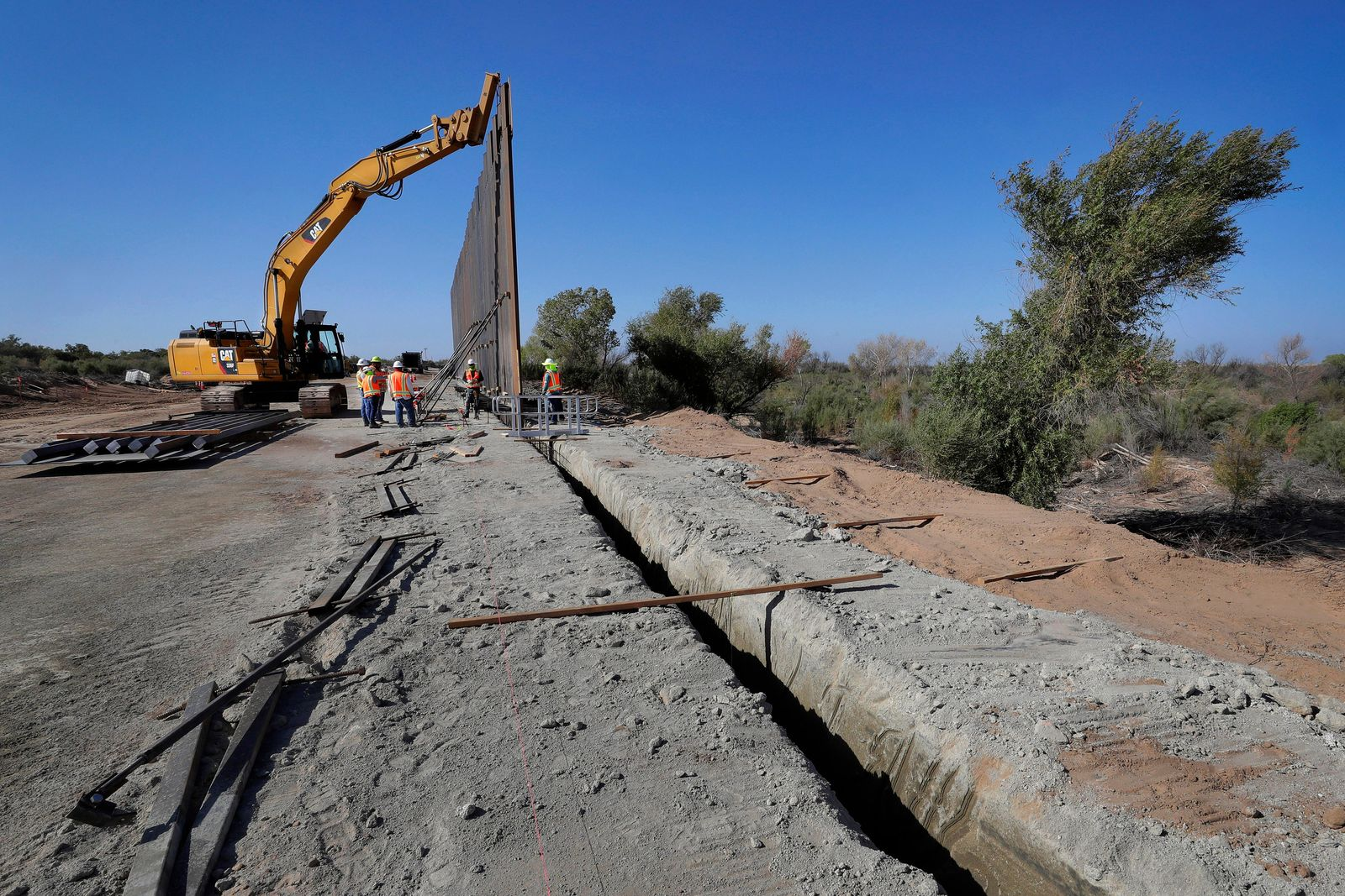 FILE - In this Sept. 10, 2019, file photo government contractors erect a section of Pentagon-funded border wall along the Colorado River, in Yuma, Ariz. A federal appeals court hears arguments against diverting Pentagon money for border wall construction as time runs out. It says the Trump administration has moved quickly to spend the money after the Supreme Court rejected an emergency appeal to prevent work from starting in July. cut to pay for President Donald Trump's wall. (AP Photo/Matt York, File)