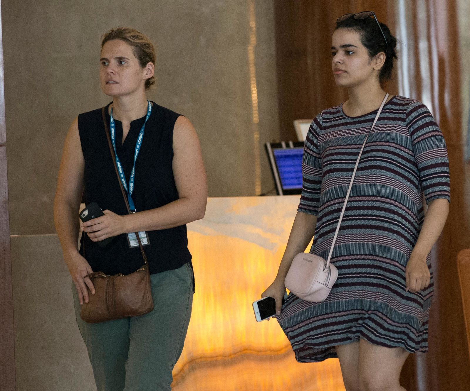 Rahaf Mohammed Alqunun, right, walks with an unidentified companion in Bangkok, Thailand, Friday, Jan. 11, (AP Photo/Sakchai Lalit)