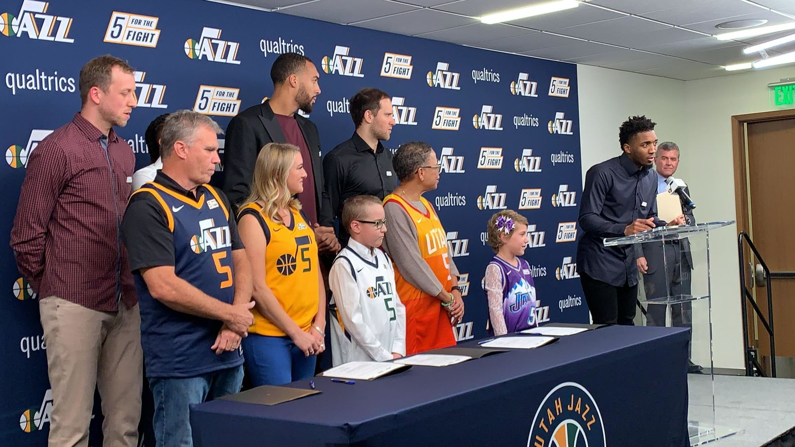 "Everyone poses for a photo op promoting ""5 For The Fight"" which aims to fund cancer research. (L-R) Joe Ingles (Jazz forward), Dave Warren (cancer fighter), Mike Conley (Jazz point guard), Dani Phillips (cancer fighter), Rudy Gobert (2-time Defensive Player of the Year, Utah Jazz Center) with Wyatt Page (young cancer fighter), Emma Houston (cancer fighter), Bojan Bogdanovic (Utah Jazz forward), Baylee Semrow (young cancer fighter) Donovan ""Spida"" Mitchell (Utah Jazz guard) (Photo: Adam Forgie, KUTV)"