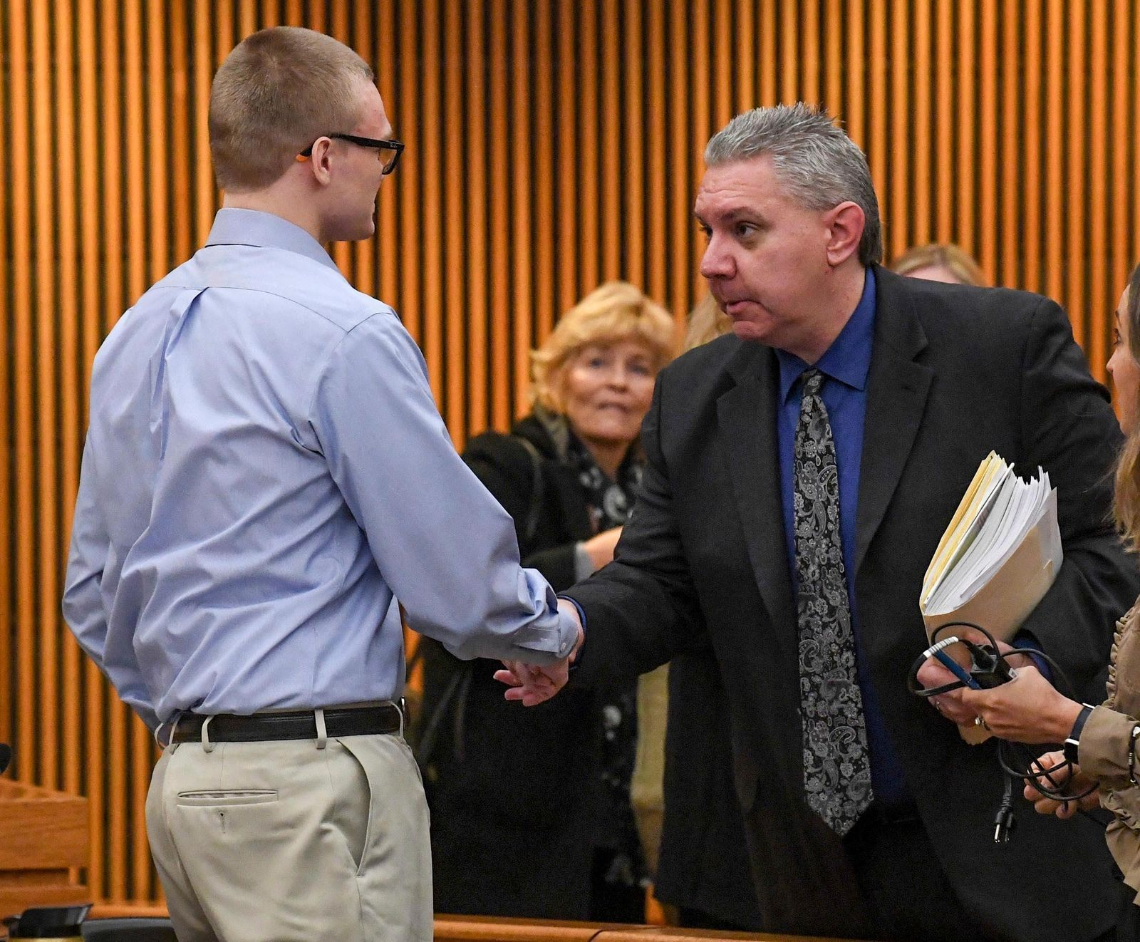 Clinical psychologist Dr. Albert Gordon Teichner, right, shakes hands with defendant Jesse Osborne after a sentence-related hearing at the Anderson County Courthouse, Wednesday, Nov. 13, 2019, in Anderson, S.C.  Osborne, a teen who killed his father at home before fatally shooting a first-grader on a South Carolina elementary school playground, is either a traumatized son who can be rehabilitated or a dangerous and pathological liar with no remorse, according to the conflicting testimony of two mental health professionals Wednesday.  (Ken Ruinard/The Independent-Mail via AP)