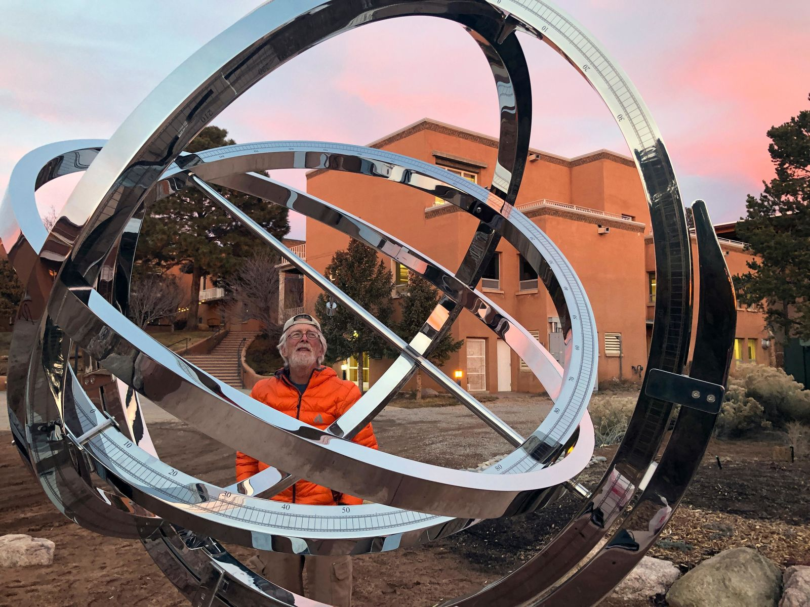 In this Dec. 11, 2019 photo Bill Donahue, a retired teacher and director of laboratories at St. John's College, uses an armillary sphere to track planetary rotations and explore the history of astronomy in Santa Fe, N.M. The unique precision-steel replica of an instrument created by Danish astonomer Tycho Brahe was commissioned by graduates of the college where students trace the evolution of math and science from early civilizations. (AP Photo/Morgan Lee)