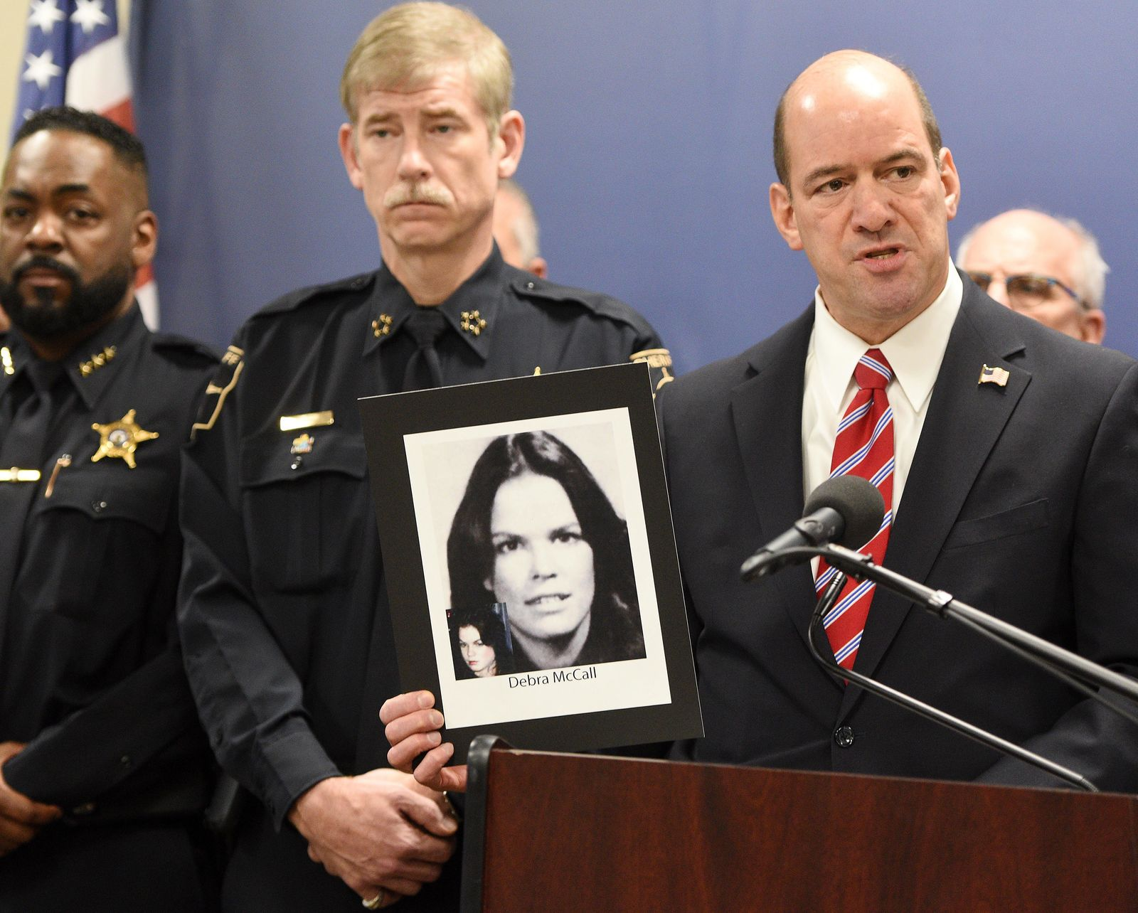 DuPage County state's attorney Robert Berlin holds up a photo of Debra McCall, a victim of an unsolved murder that they thought the suspect was Bruce Lindahl, as he spoke during a press conference in Wheaton, Ill., Monday, Jan. 13, 2020. Lindahl strangled a suburban Chicago teenage girl in 1976 and likely killed McCall just days before she was to testify in court that he raped her, police said Monday. (Rick West/Daily Herald via AP)