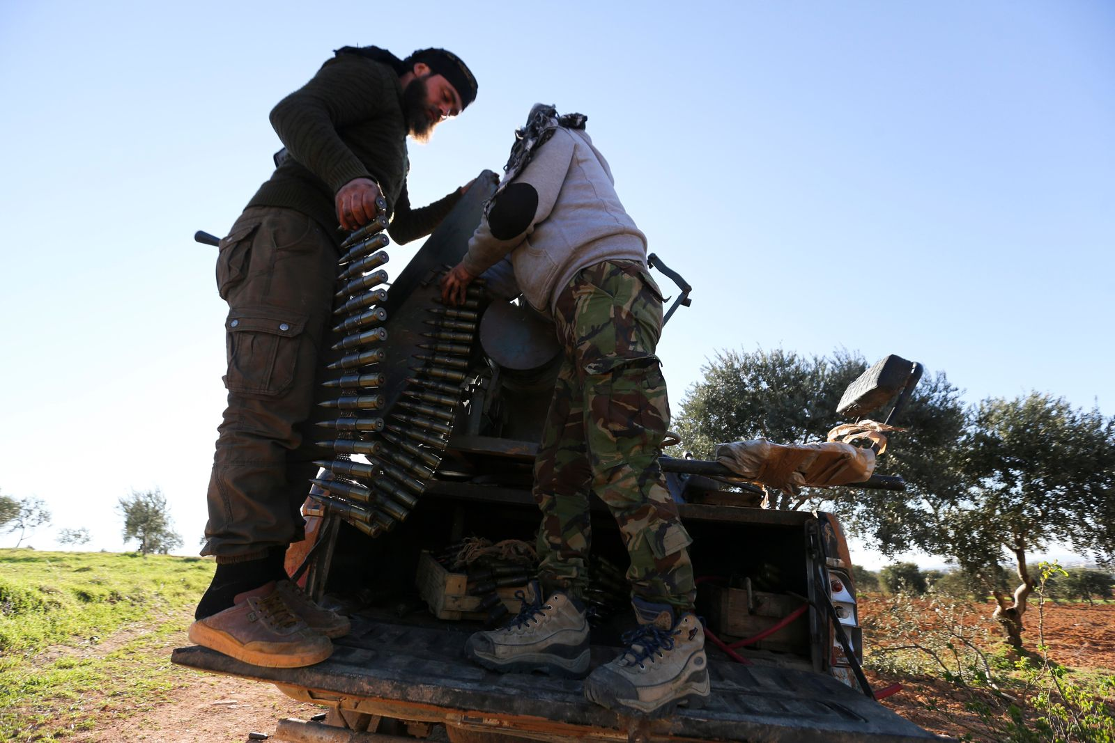 Turkish backed Syrian fighters load ammunition at a frontline near the town of Saraqib in Idlib province, Syria, Wednesday, Feb. 26, 2020. Syrian government forces have captured dozens of villages, including major rebel strongholds, over the past few days{ }in the last opposition-held area in the country's northwest. (AP Photo/Ghaith Alsayed)