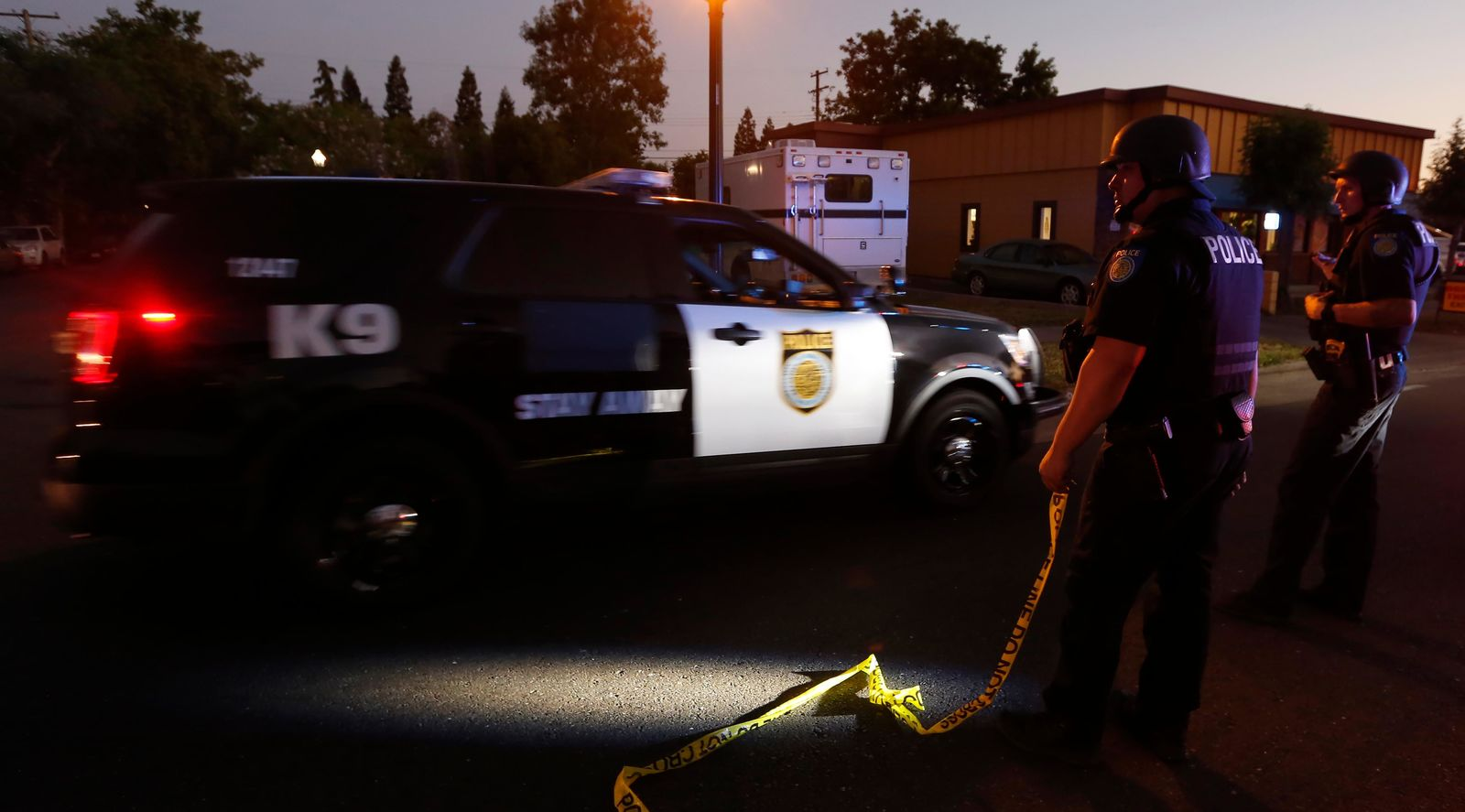 A Sacramento Police vehicle passes a roadblock near a home that authorities have surrounded where an armed suspect has taken refuge after shooting a Sacramento police officer, Wednesday, June 19, 2019, in Sacramento, Calif. (AP Photo/Rich Pedroncelli)