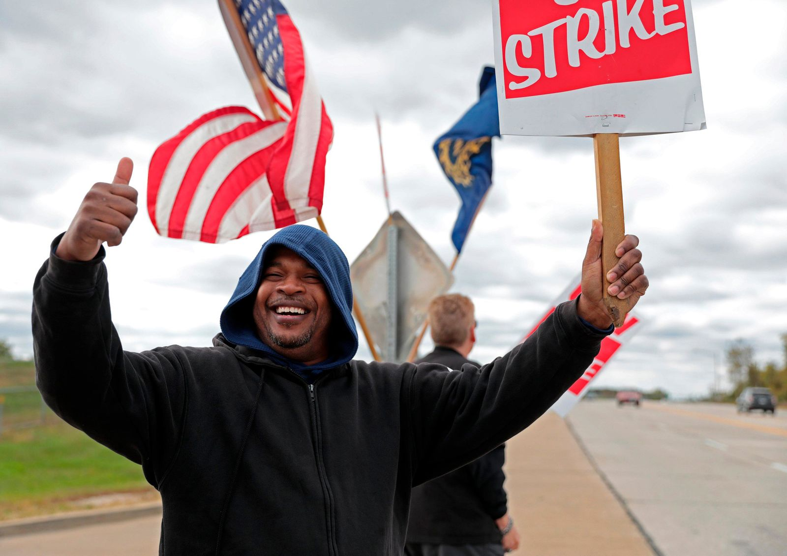Bill Jackson, of St. Louis, gives a thumbs up to drivers that wave or honk as United Auto Workers outside the GM{ }Wentzville Assembly Center in Wentzville, Mo.,  Wednesday, Oct. 16, 2019. UAW workers have been on strike since Sept. 16, but have reached a tentative deal with GM today. Workers expressed cautious optimism, but will likely remain on the picket line until an official deal has been reached. (Cristina M. Fletes/St. Louis Post-Dispatch via AP)