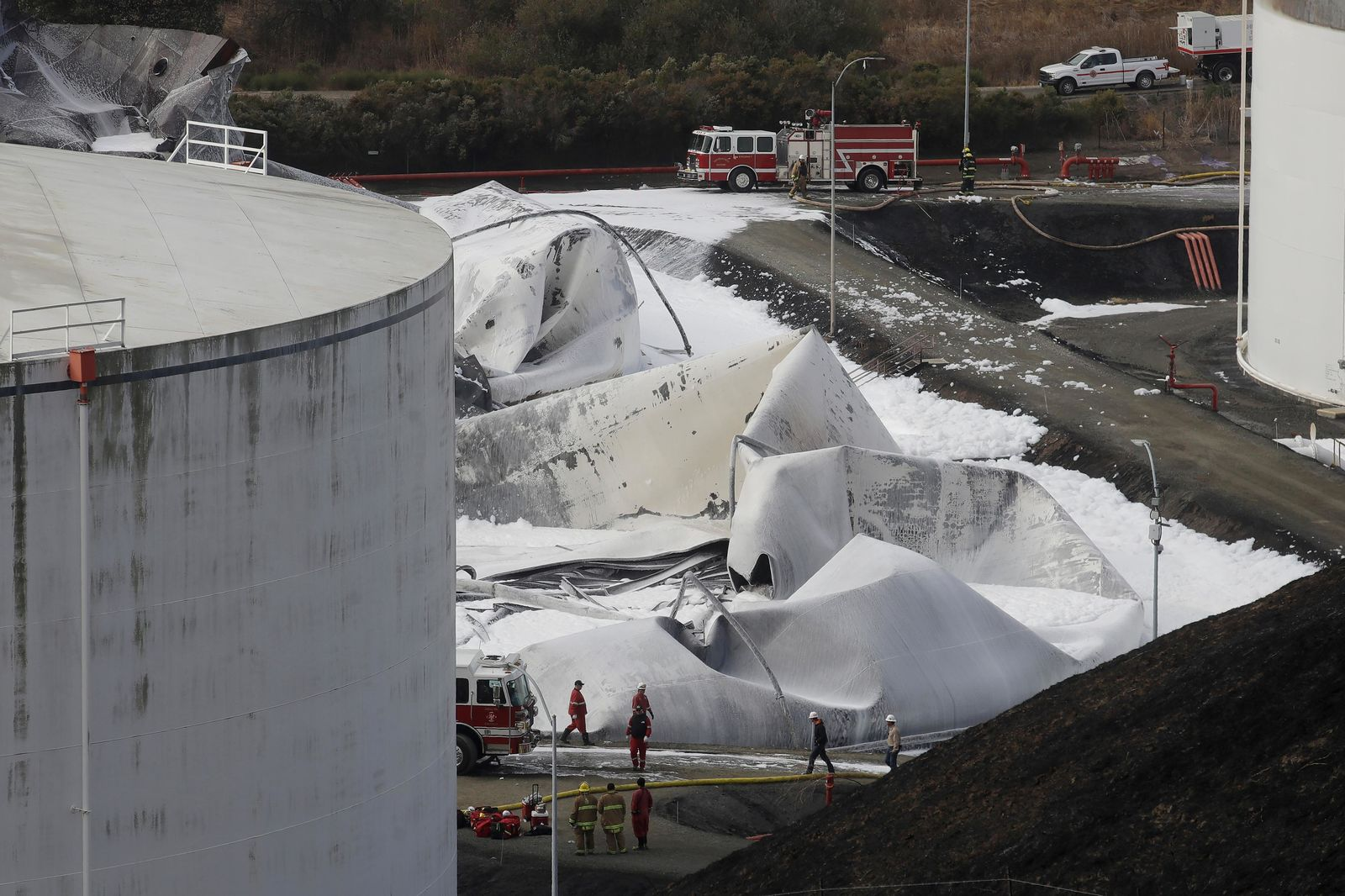Fire and emergency crews walk past damage at NuStar Energy fuel storage facility, Wednesday, Oct. 16, 2019, in Crockett, Calif. Officials are trying to determine if a 4.5 magnitude earthquake the day before triggered an explosion at the facility. (AP Photo/Jeff Chiu)