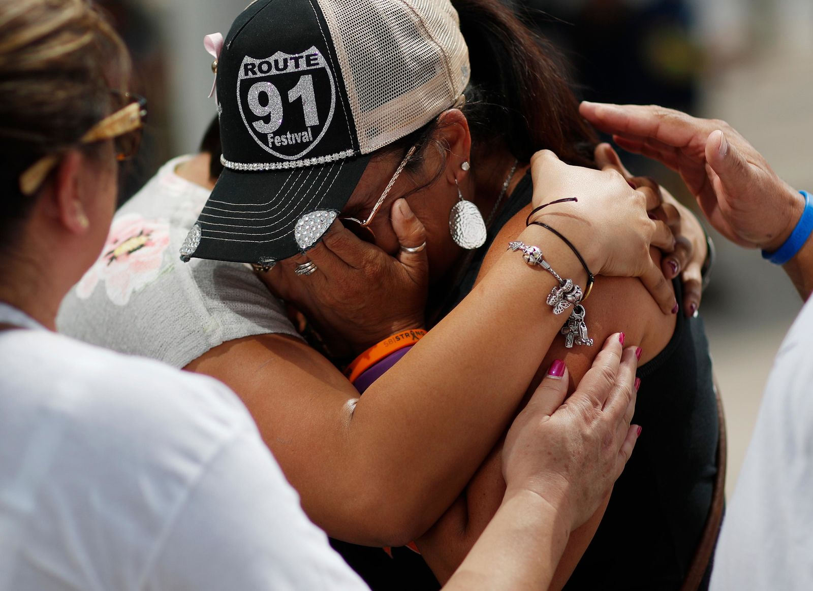 FILE - In this Oct. 1, 2018 file photo people embrace Norma Felix at a prayer service on the anniversary of the Oct.1, 2017 mass shooting in Las Vegas. (AP Photo/John Locher,File)