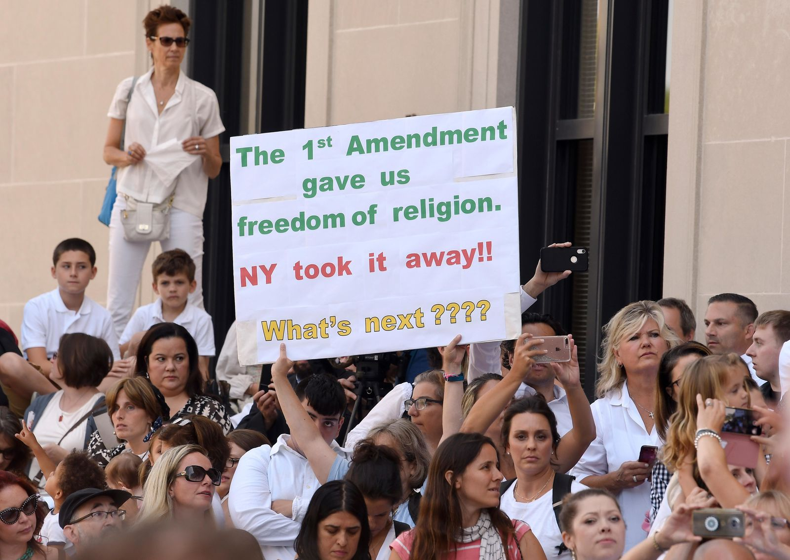 FILE - In this Aug. 14, 2019, file photo, people wait in line to hear attorneys speak at a hearing challenging the constitutionality of the state legislature's repeal of the religious exemption to vaccination outside the Albany County Courthouse in Albany, N.Y. (AP Photo/Hans Pennink, File)
