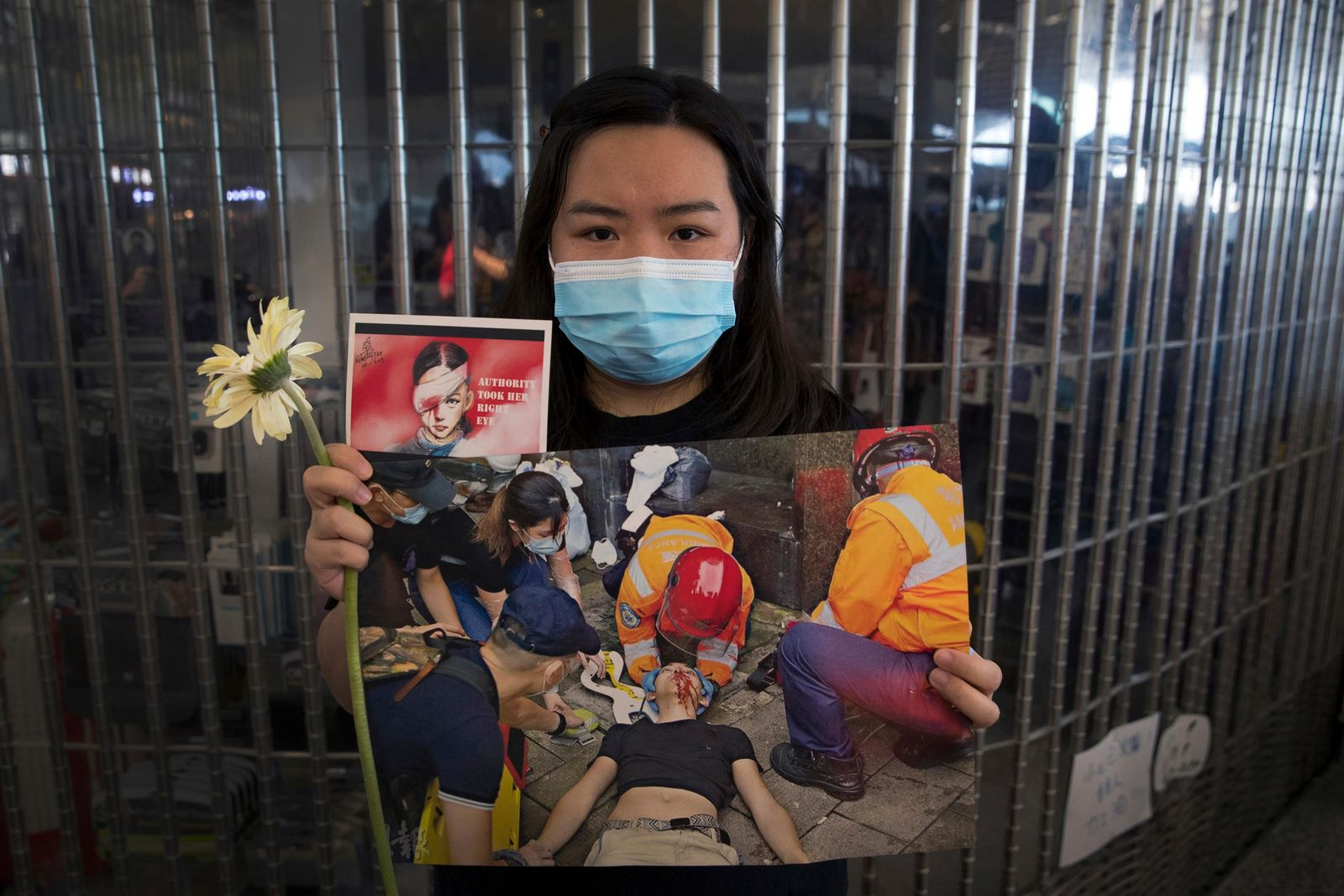 A woman holds a flower and posters showing people injured by police as protesters stage a sit-in rally at he Hong Kong International Airport in Hong Kong, Tuesday, Aug. 13, 2019. Protesters clogged the departure area at Hong Kong's reopened airpor