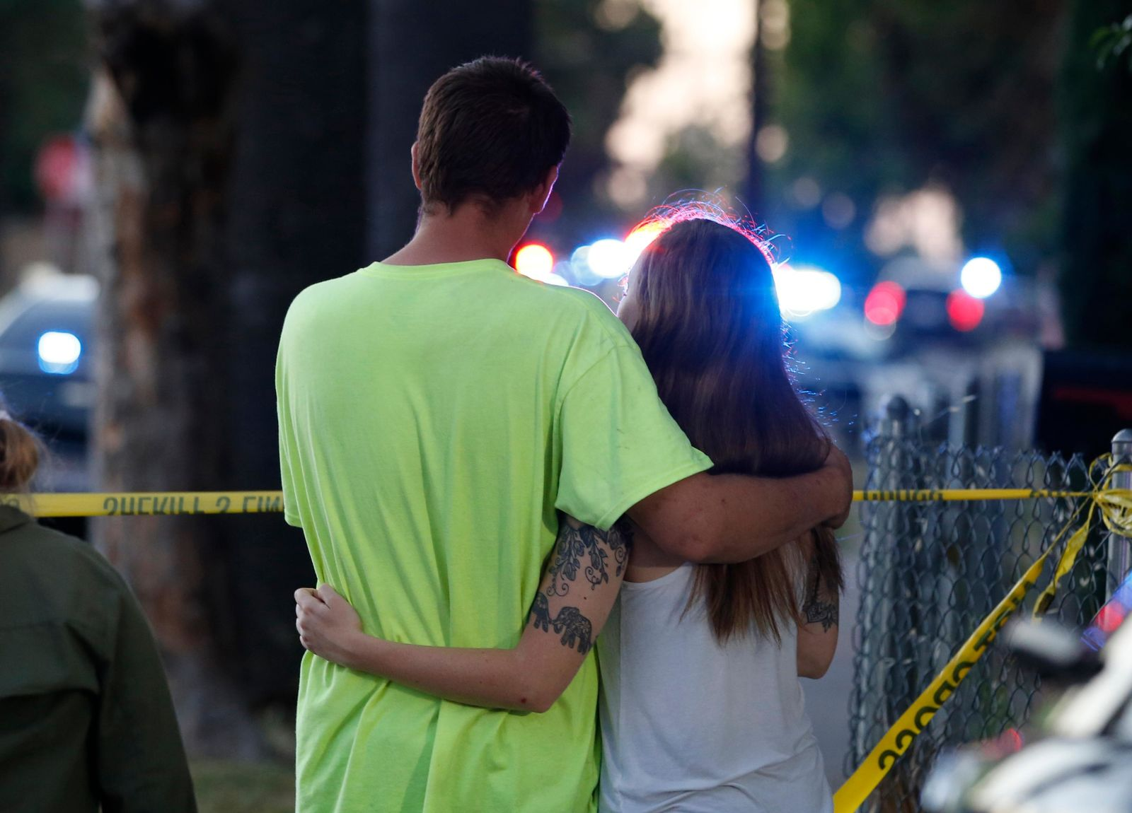 A man and woman watch as law enforcement officers surround a home where a gunman has taken refuge after shooting a Sacramento police officer, Wednesday, June 19, 2019, in Sacramento, Calif. (AP Photo/Rich Pedroncelli)