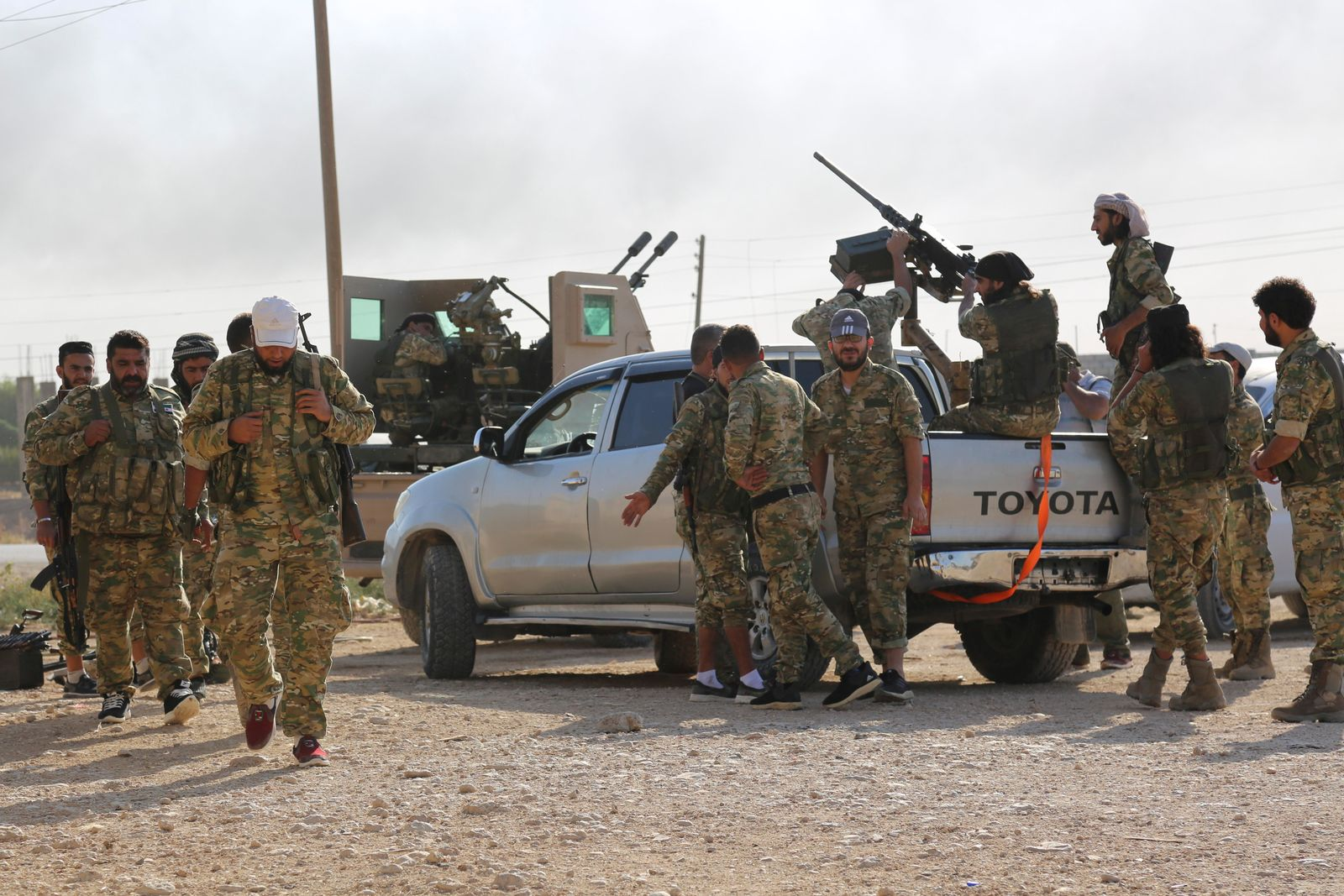 In this Saturday, Oct. 12, 2019 photo, Turkey-backed Syrian fighters enter Ras al-Yan, Syria.Turkey's military says it has captured a key Syrian border town Ras al-Ayn under heavy bombardment in its most significant gain as its offensive against Kurdish fighters presses into its fourth day. (AP Photo)